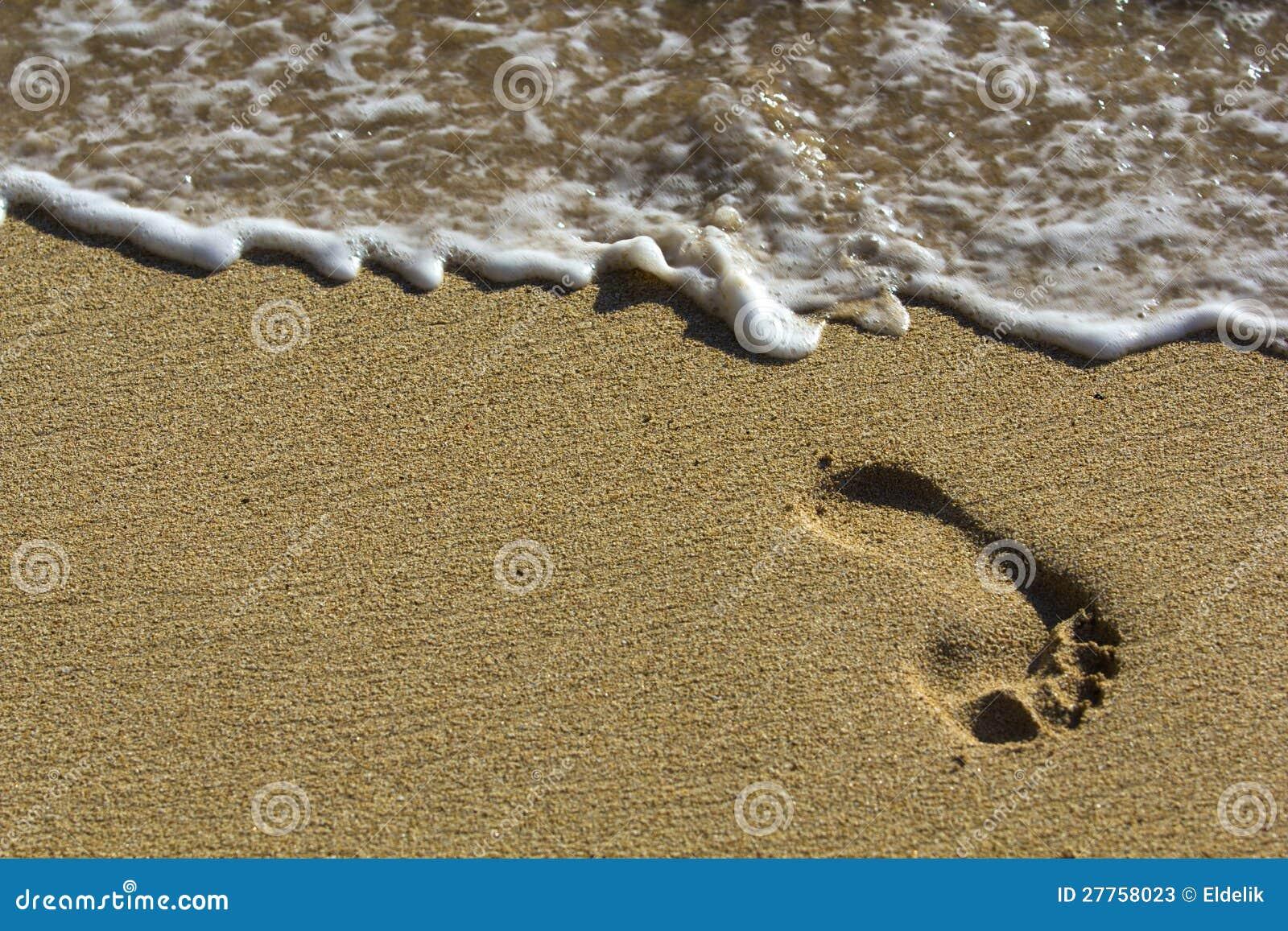 Empreinte de pas à la plage avec des vagues