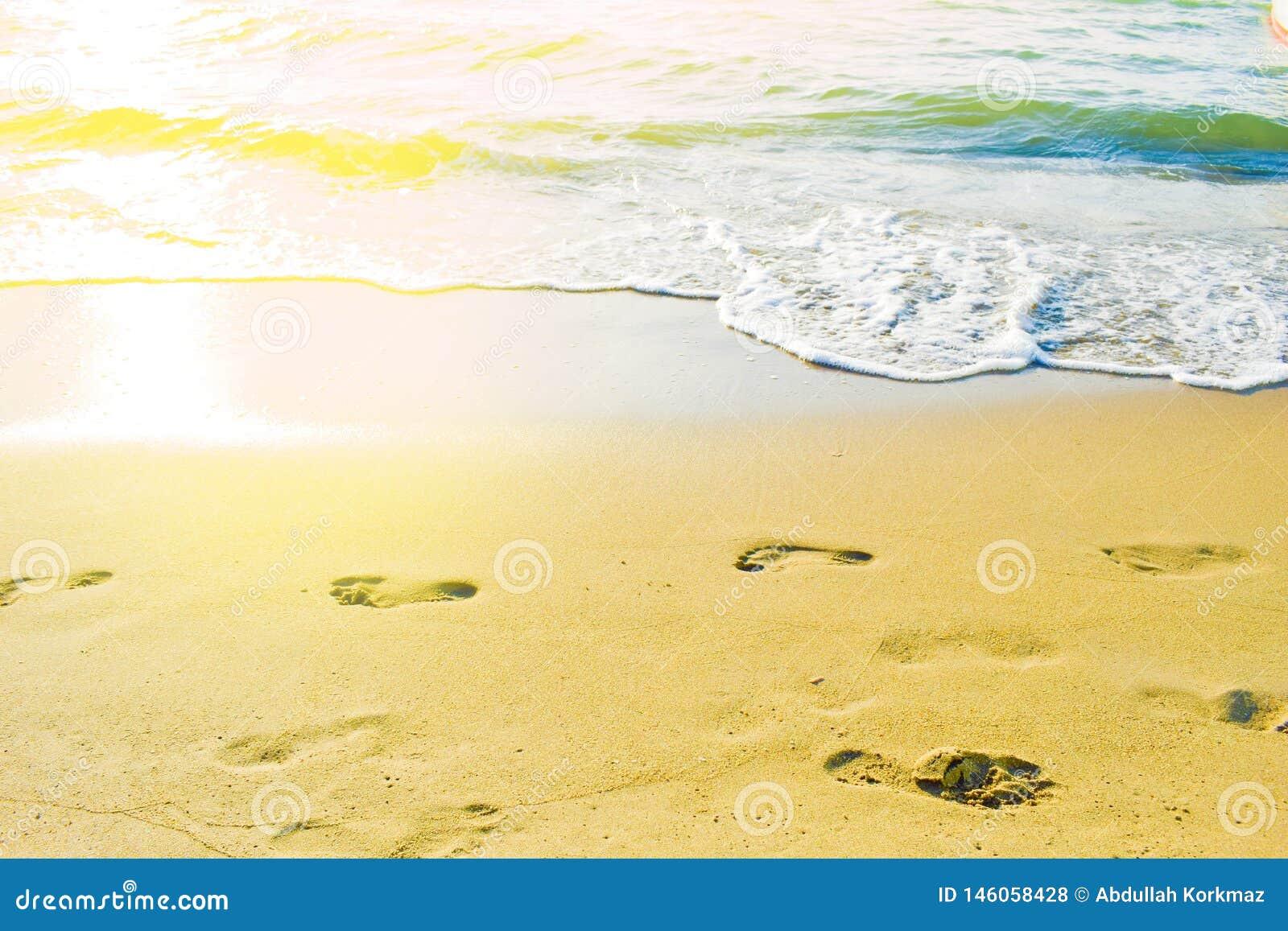 Empreintes de pas femelles sur la plage contre vers la mer