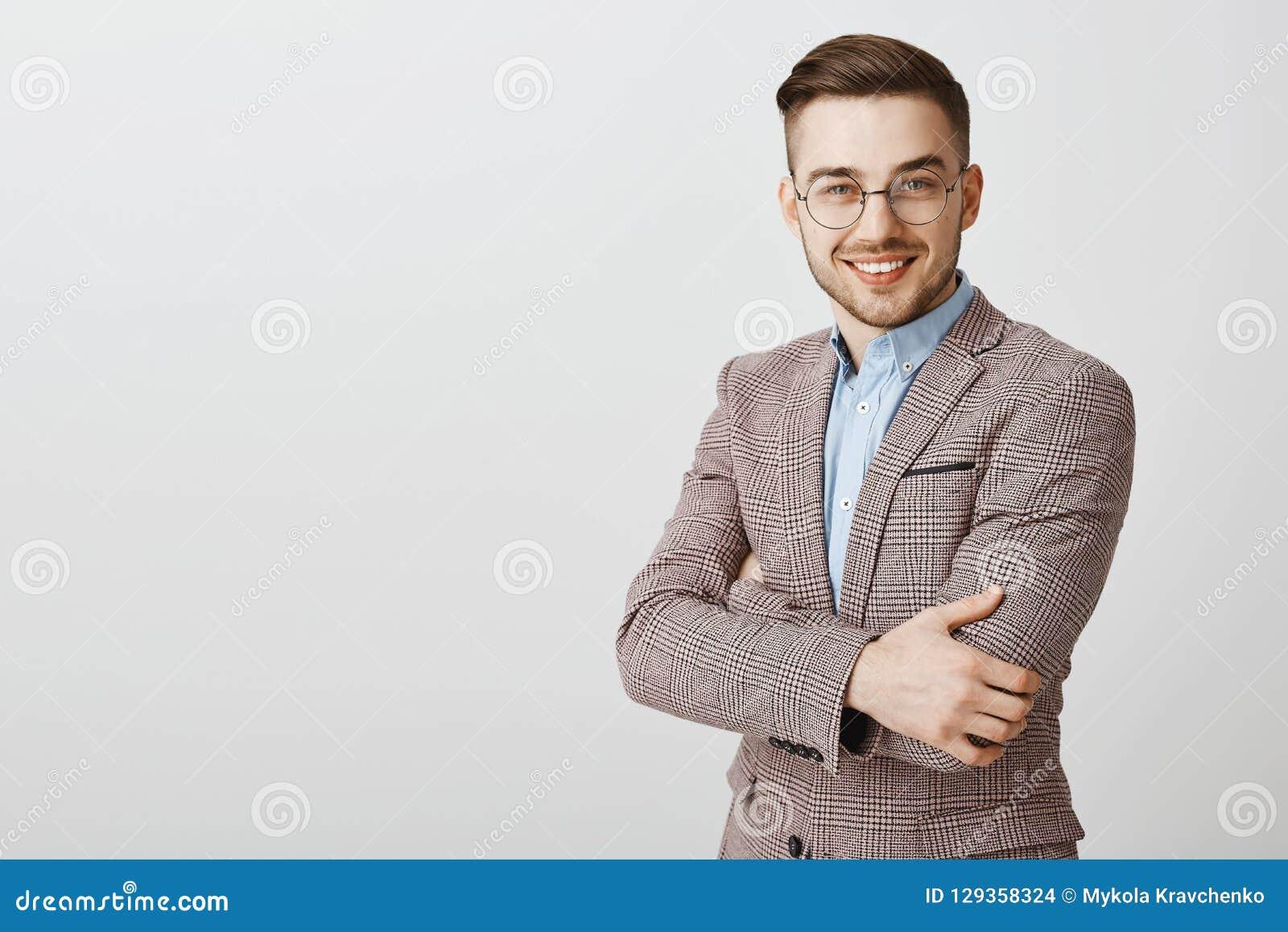 Empresário masculino europeu bonito esperto e inteligente ambicioso nos vidros e nas mãos à moda do cruzamento do revestimento so