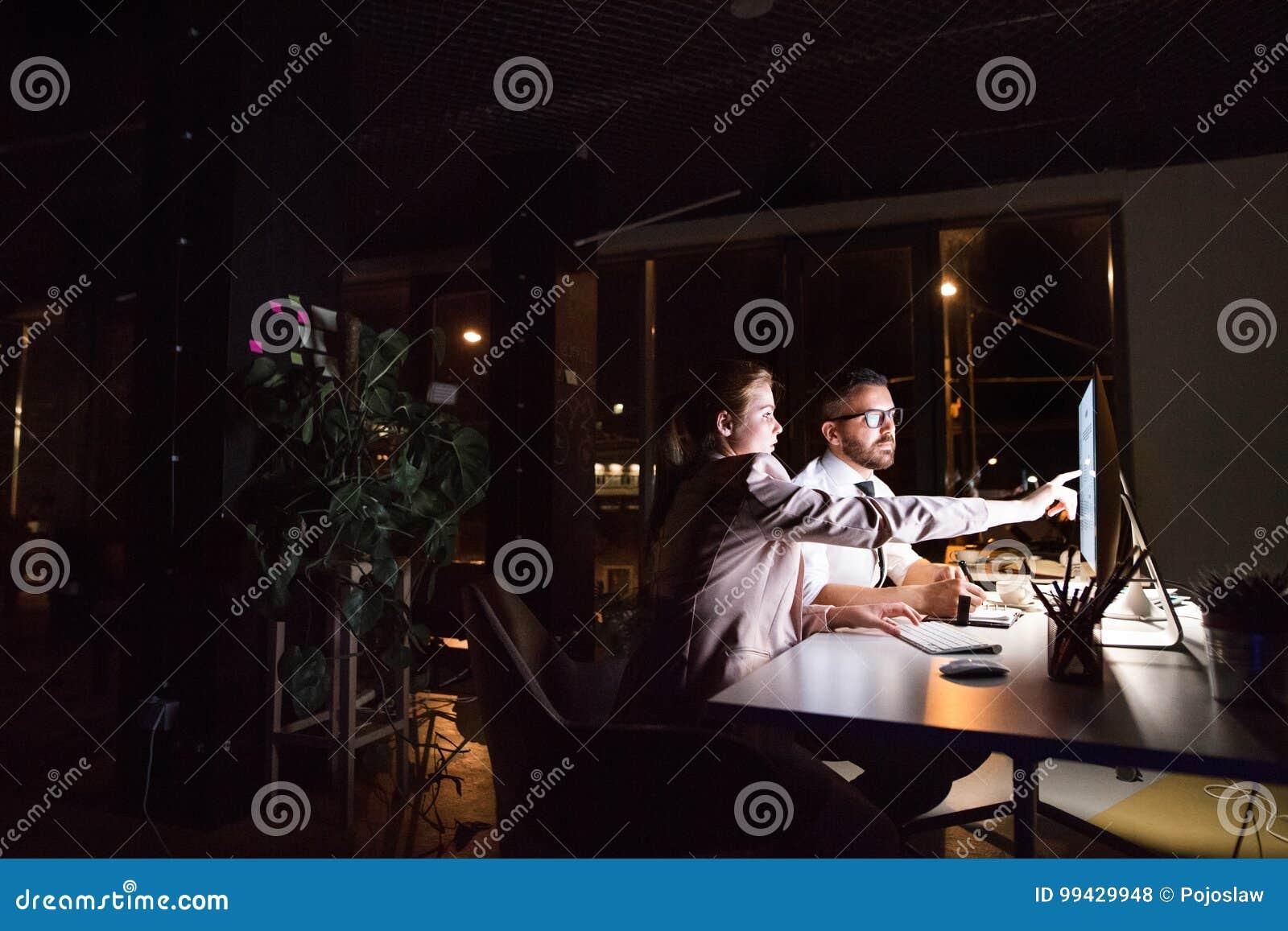 Empresários no escritório na noite que trabalha tarde