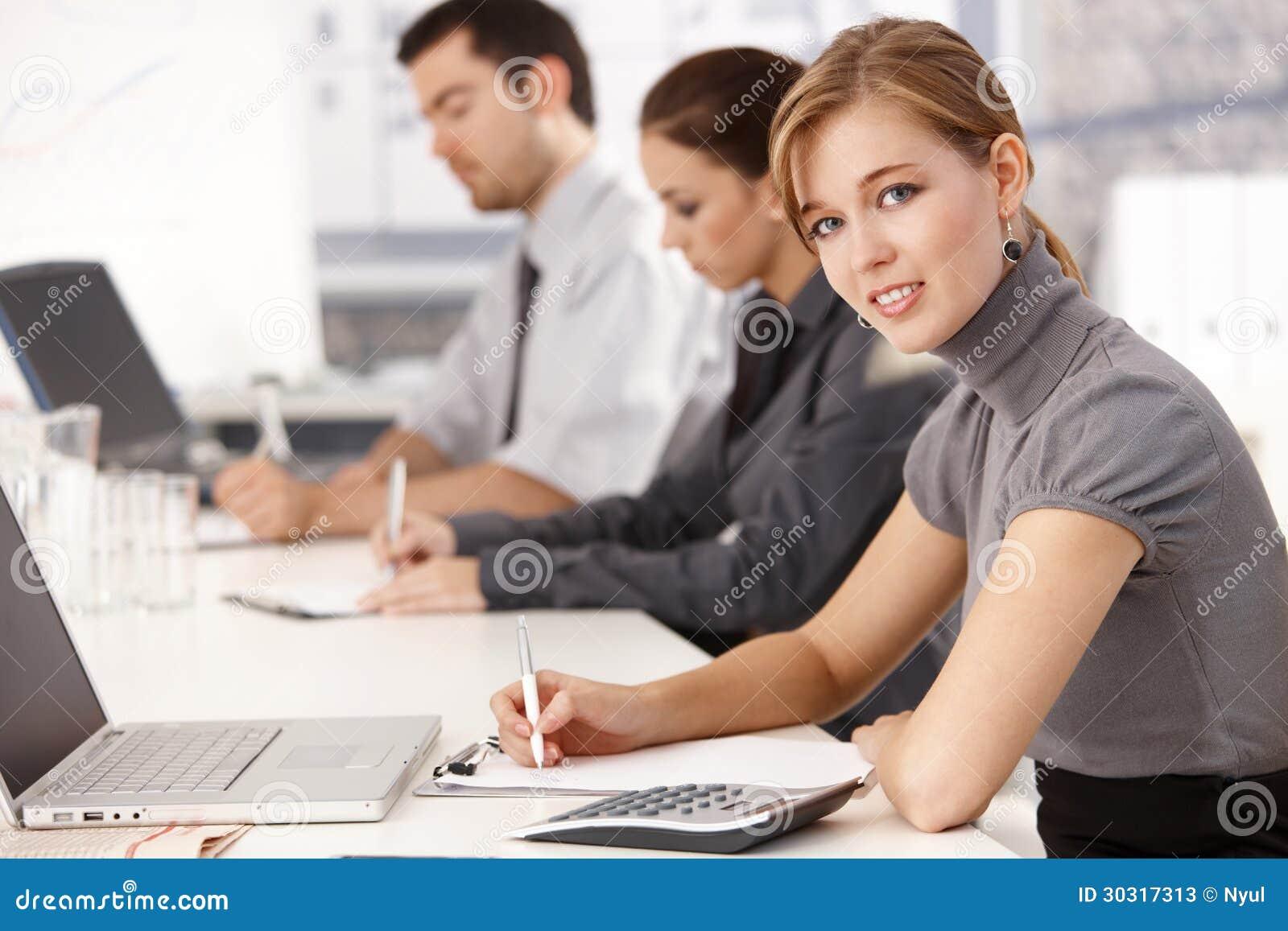 Empresários novos que sentam-se na tabela de reunião
