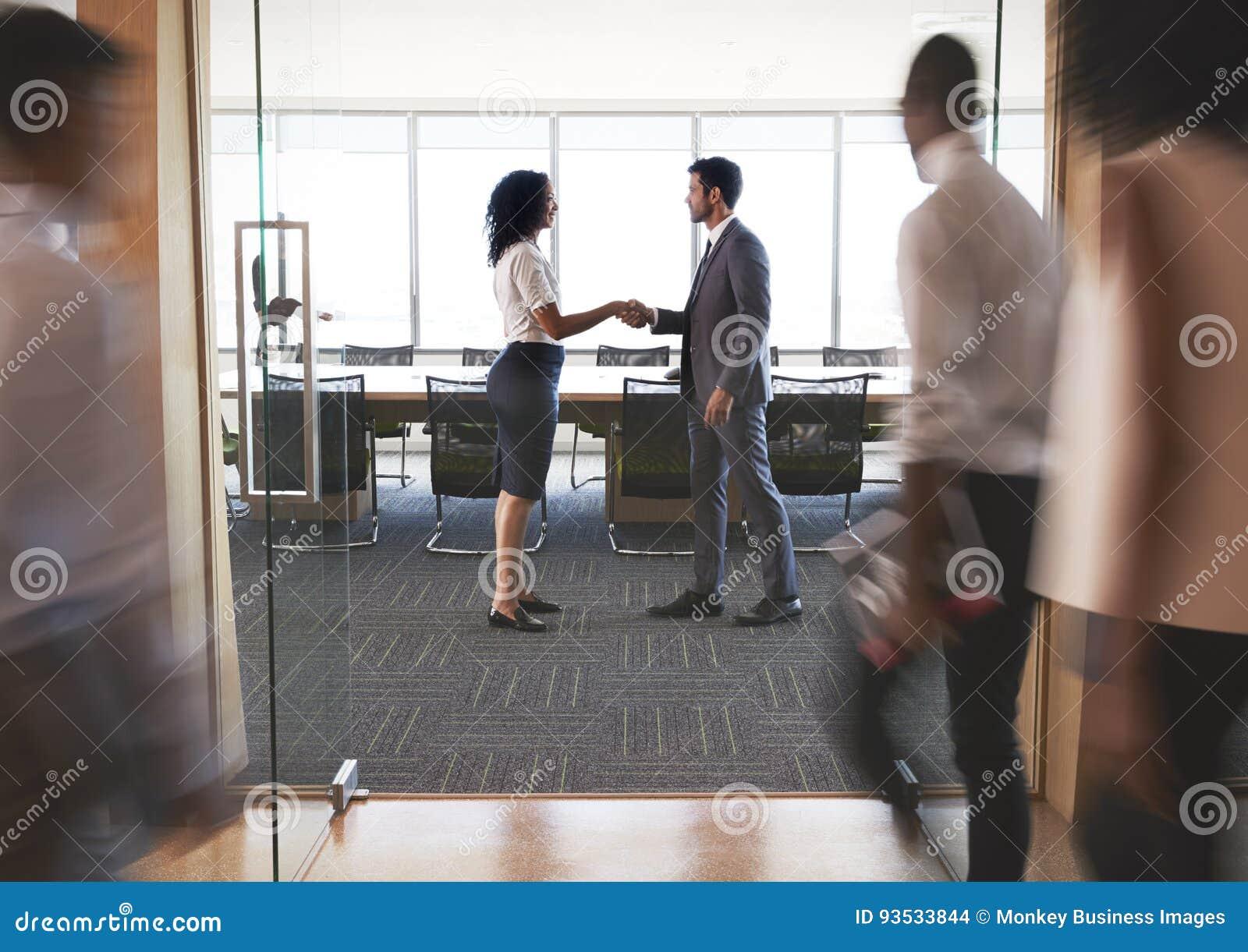 Empresários que agitam as mãos na entrada à sala de reuniões