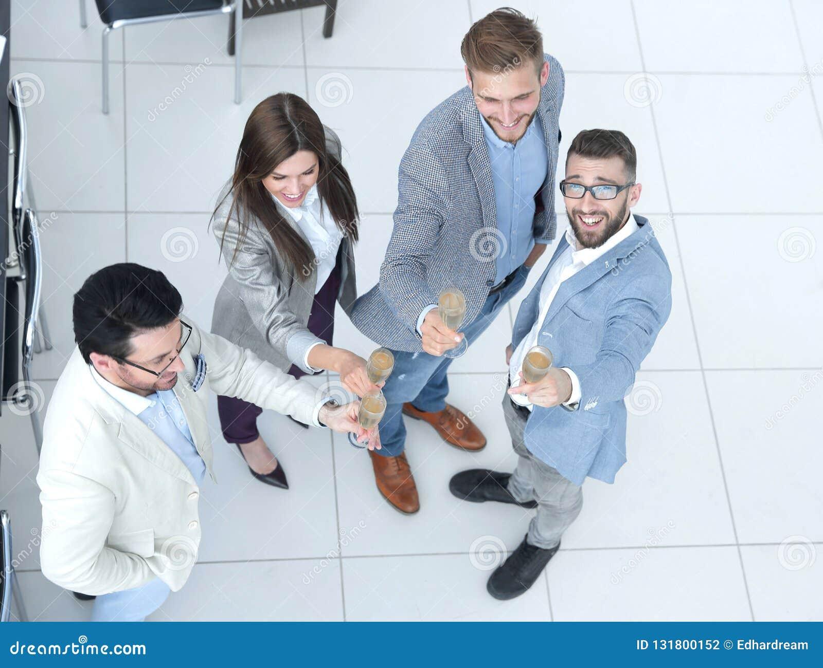 Empresários que brindam vidros do champanhe no escritório