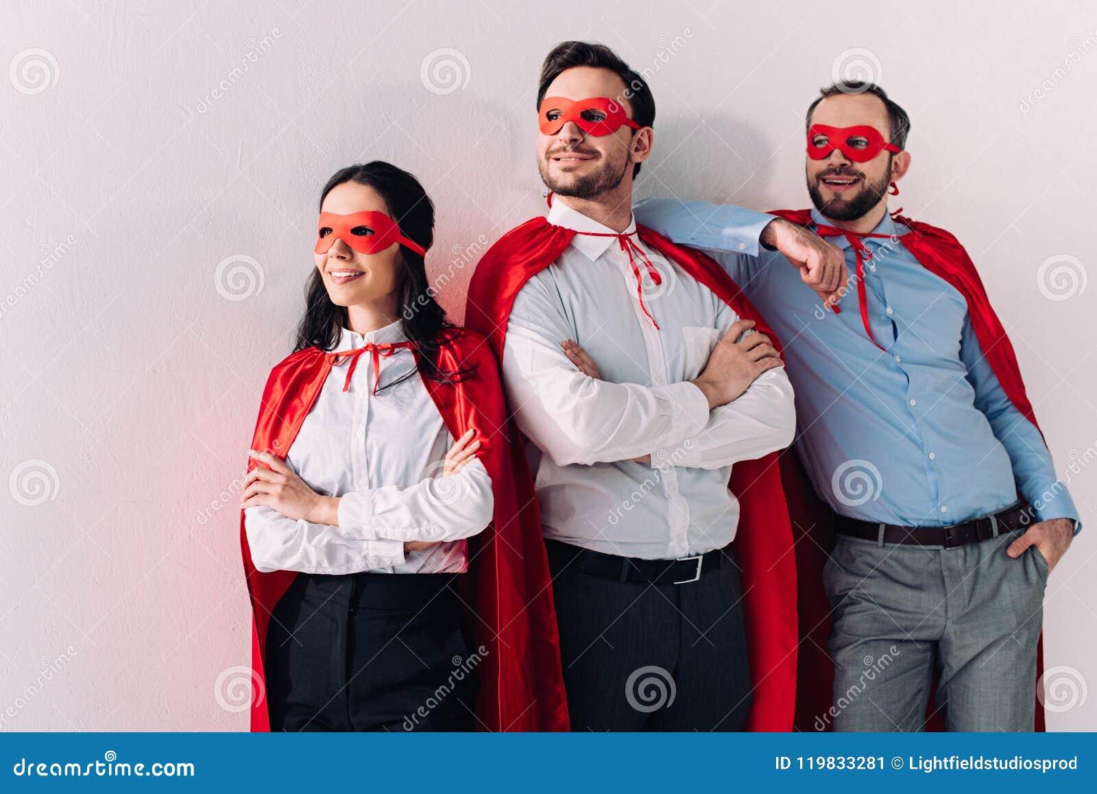 Empresários super de sorriso nas máscaras e cabos que olham afastado