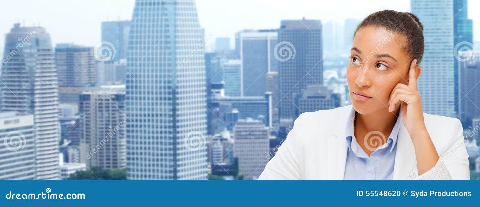 Empresaria africana que mira para arriba y que piensa