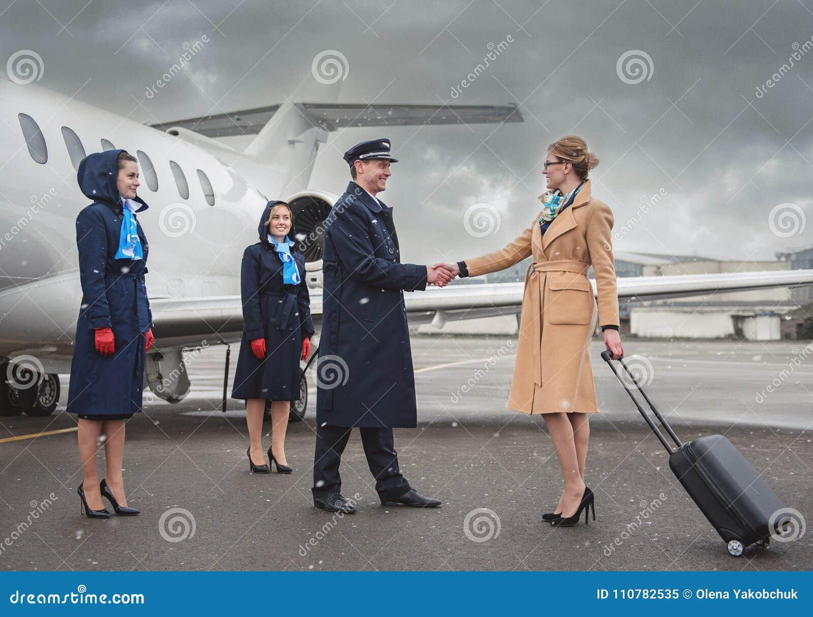 Empresaria alegre que sacude al aviador de las manos cerca del avión