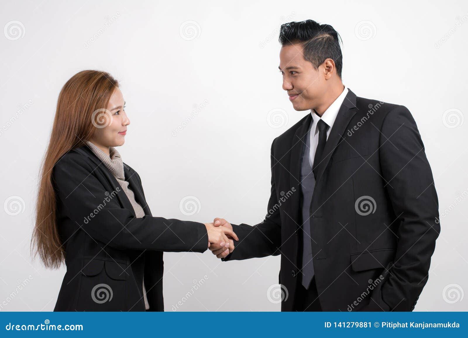 Empresaria asiática bonita que sacude al hombre de negocios de las manos para sellar un trato con su socio en un fondo blanco
