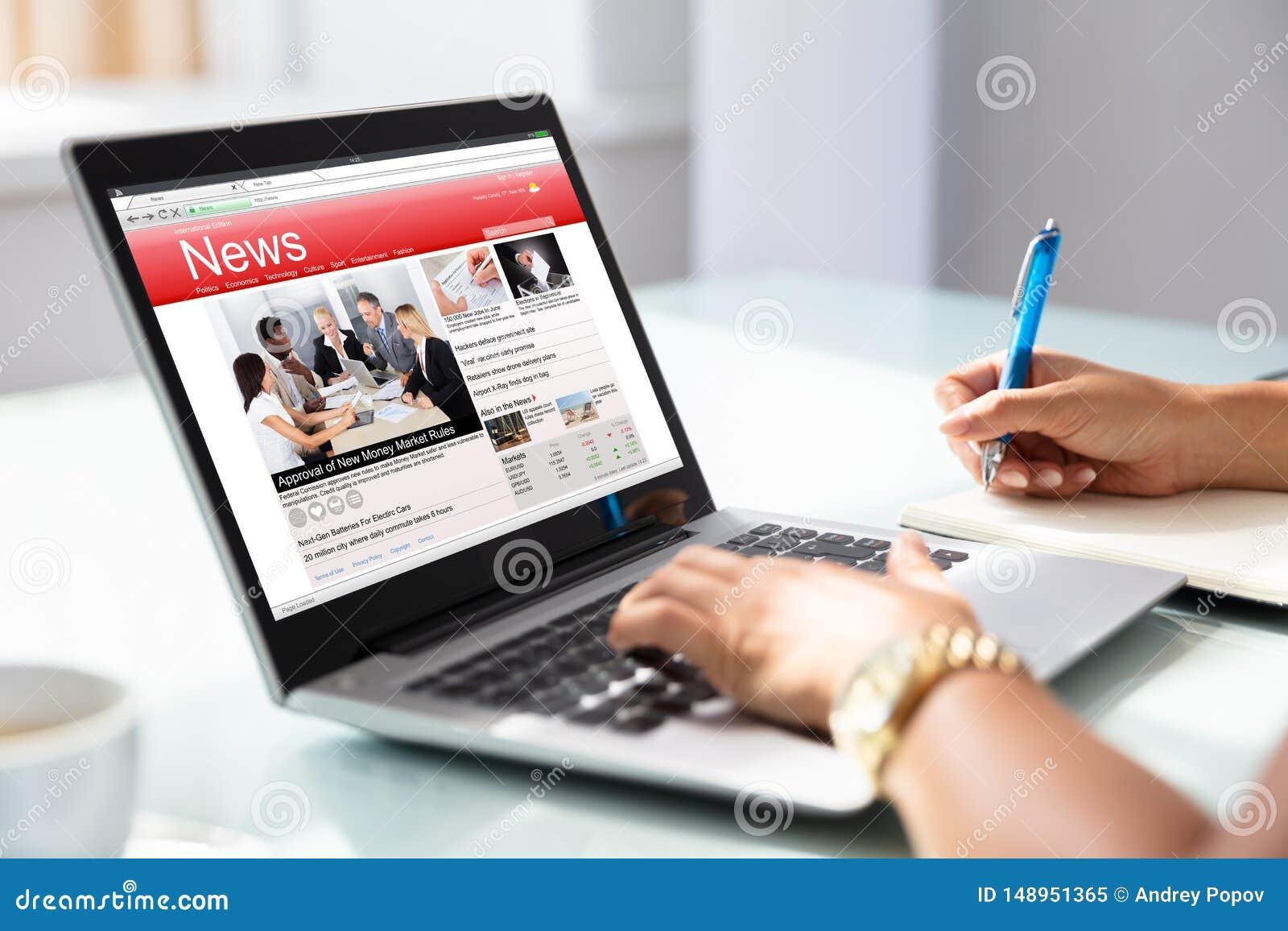 Empresaria Checking Online News en el ordenador port?til