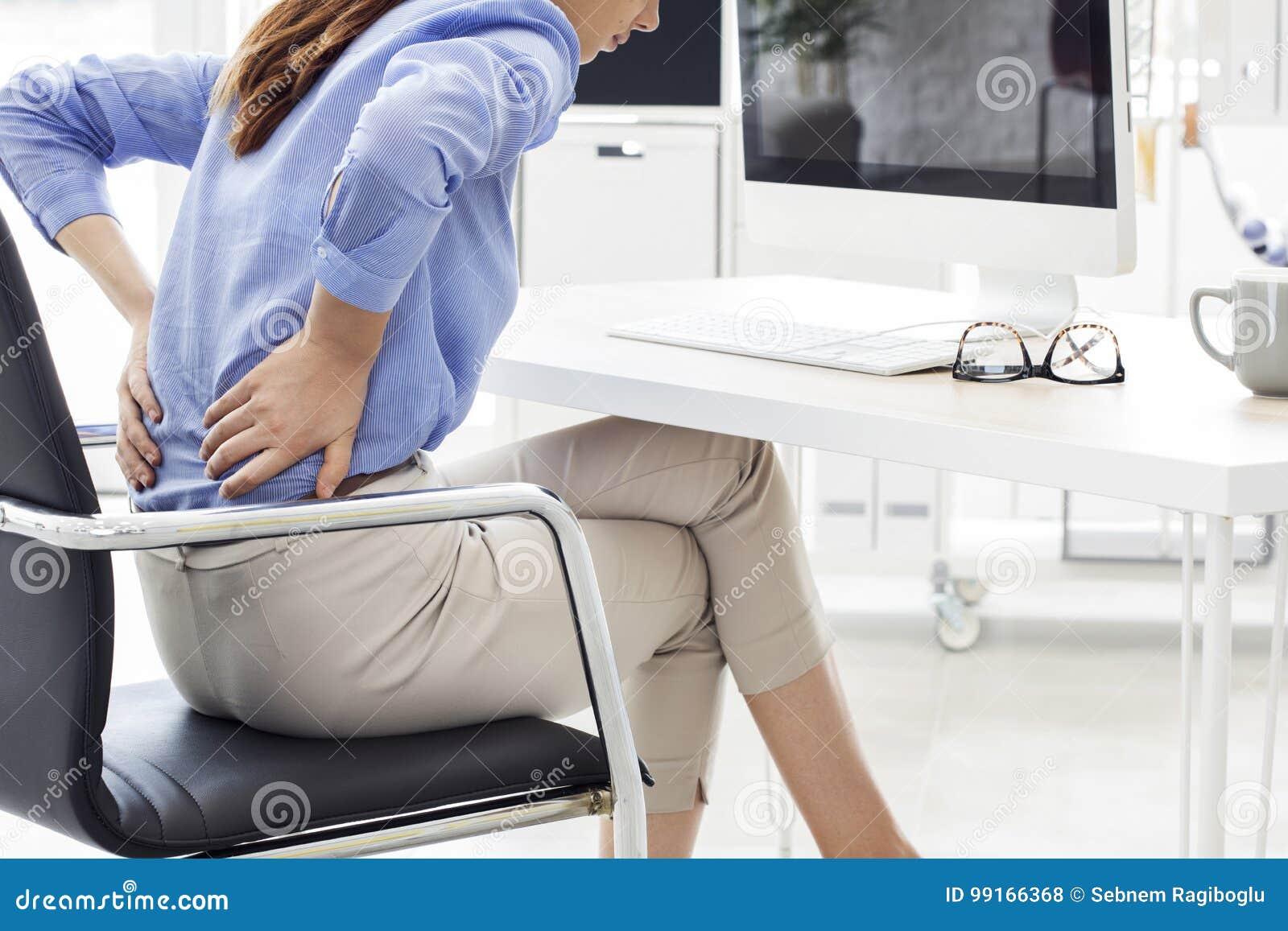 Empresaria con dolor de espalda en oficina