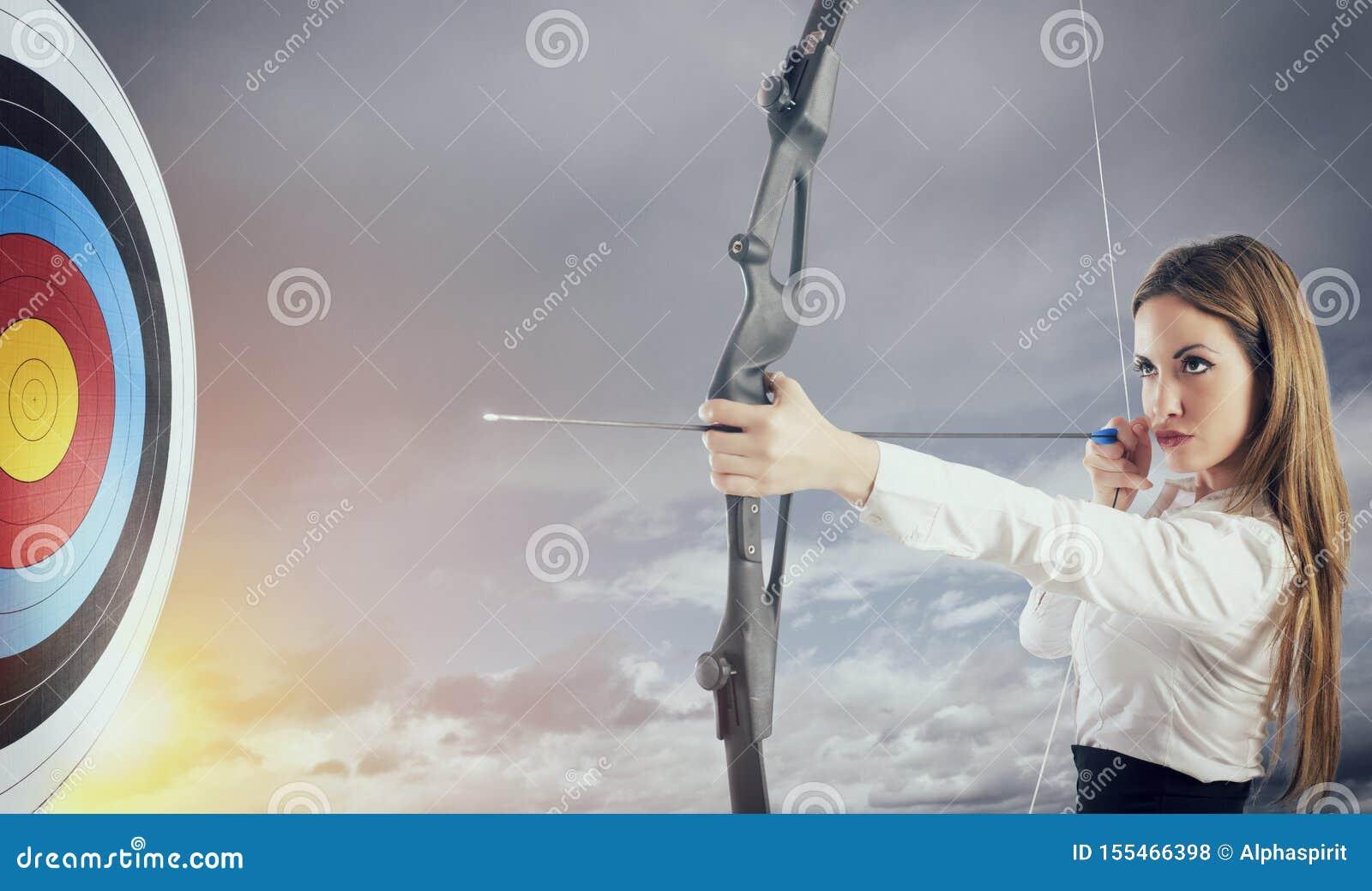 Empresaria con el arco y la flecha que se?ala el centro de la blanco