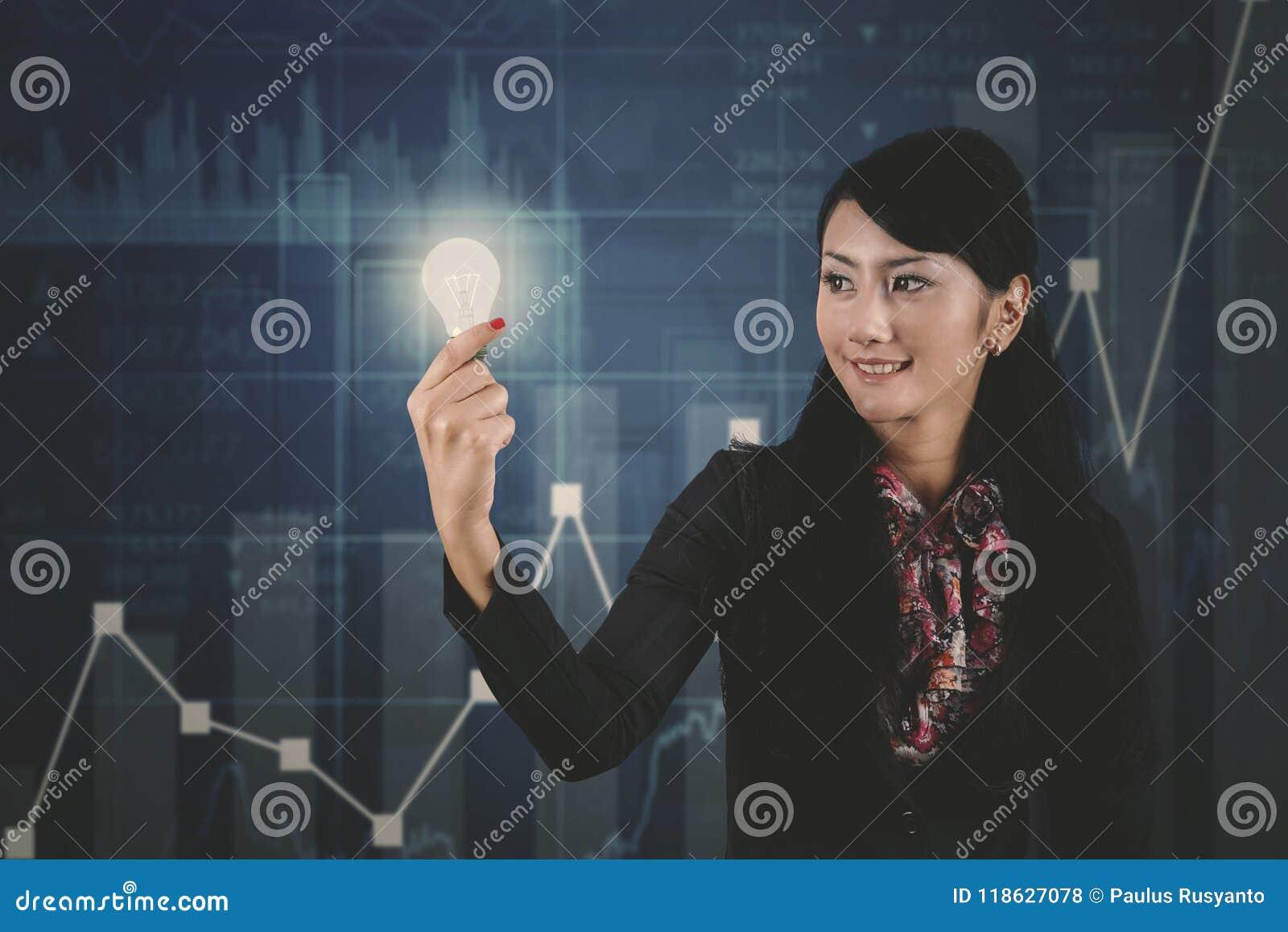 Empresaria con el gráfico brillante del bulbo y del crecimiento