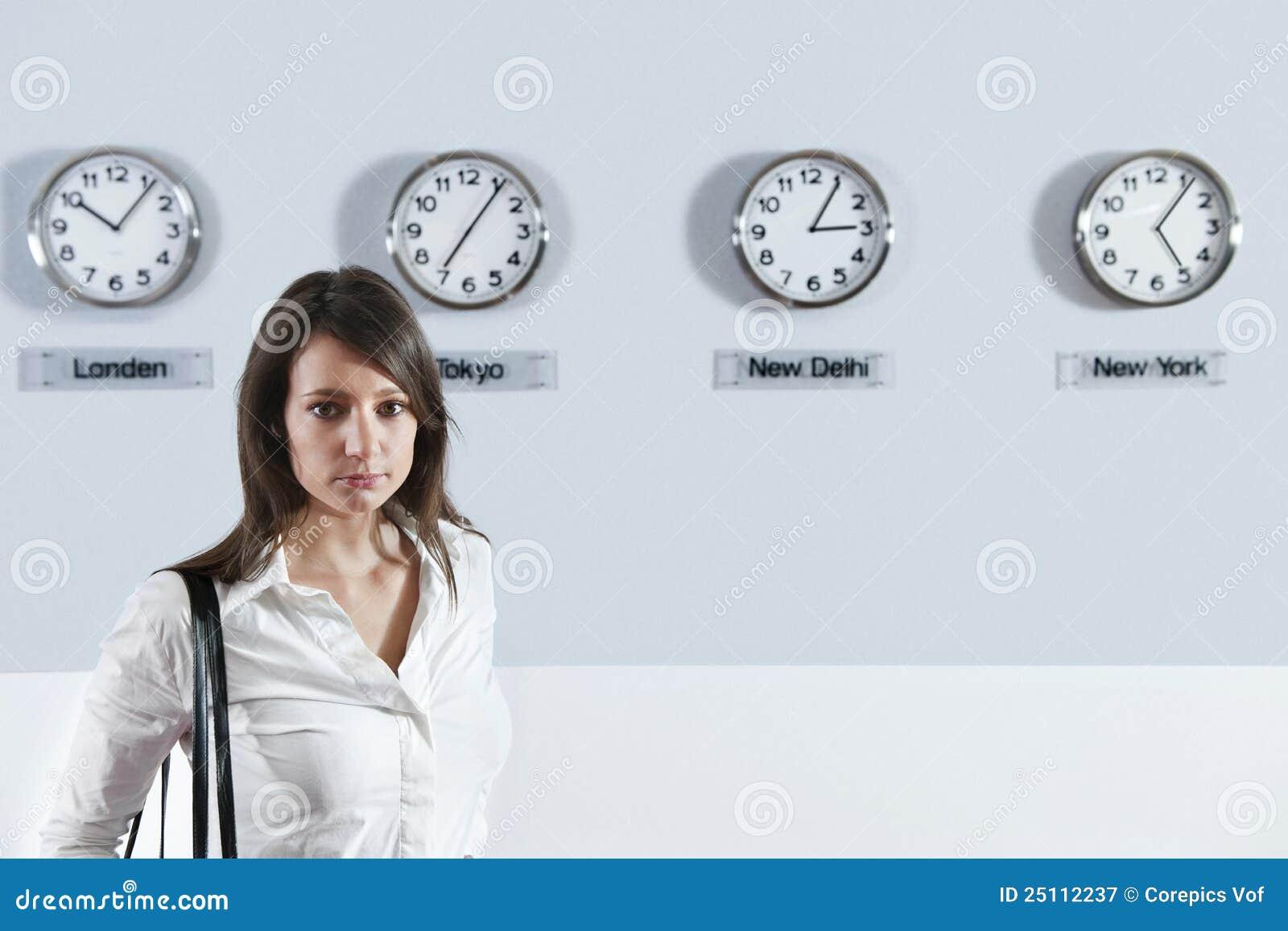 Empresaria delante de los relojes de la zona horaria del mundo