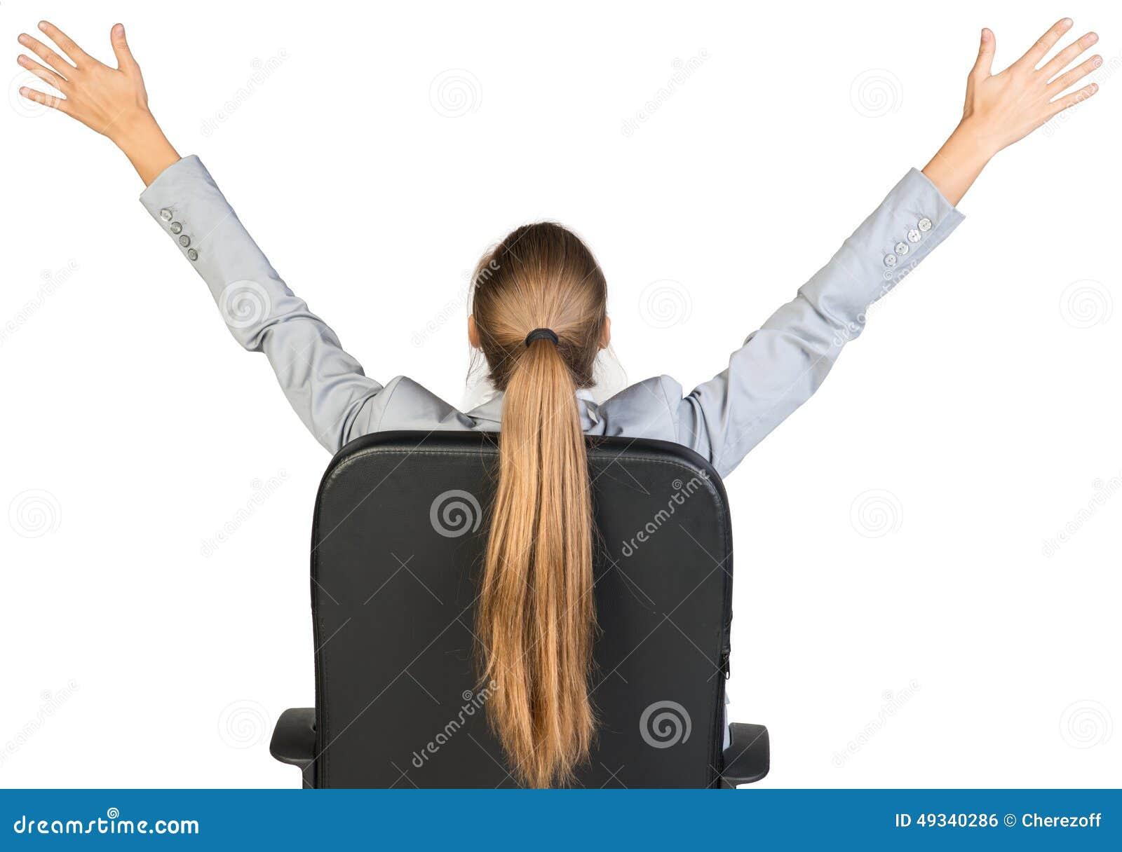 Empresaria en la silla de la oficina que estira sus brazos