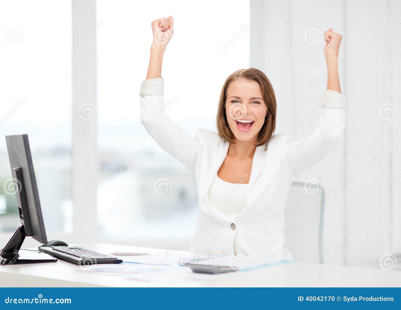 Empresaria feliz con el ordenador en oficina