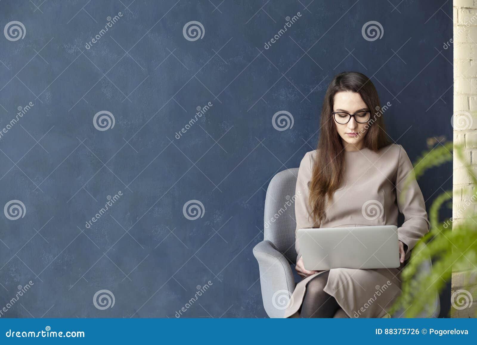 Empresaria hermosa que trabaja en el ordenador portátil mientras que se sienta en oficina moderna del desván Fondo azul marino de