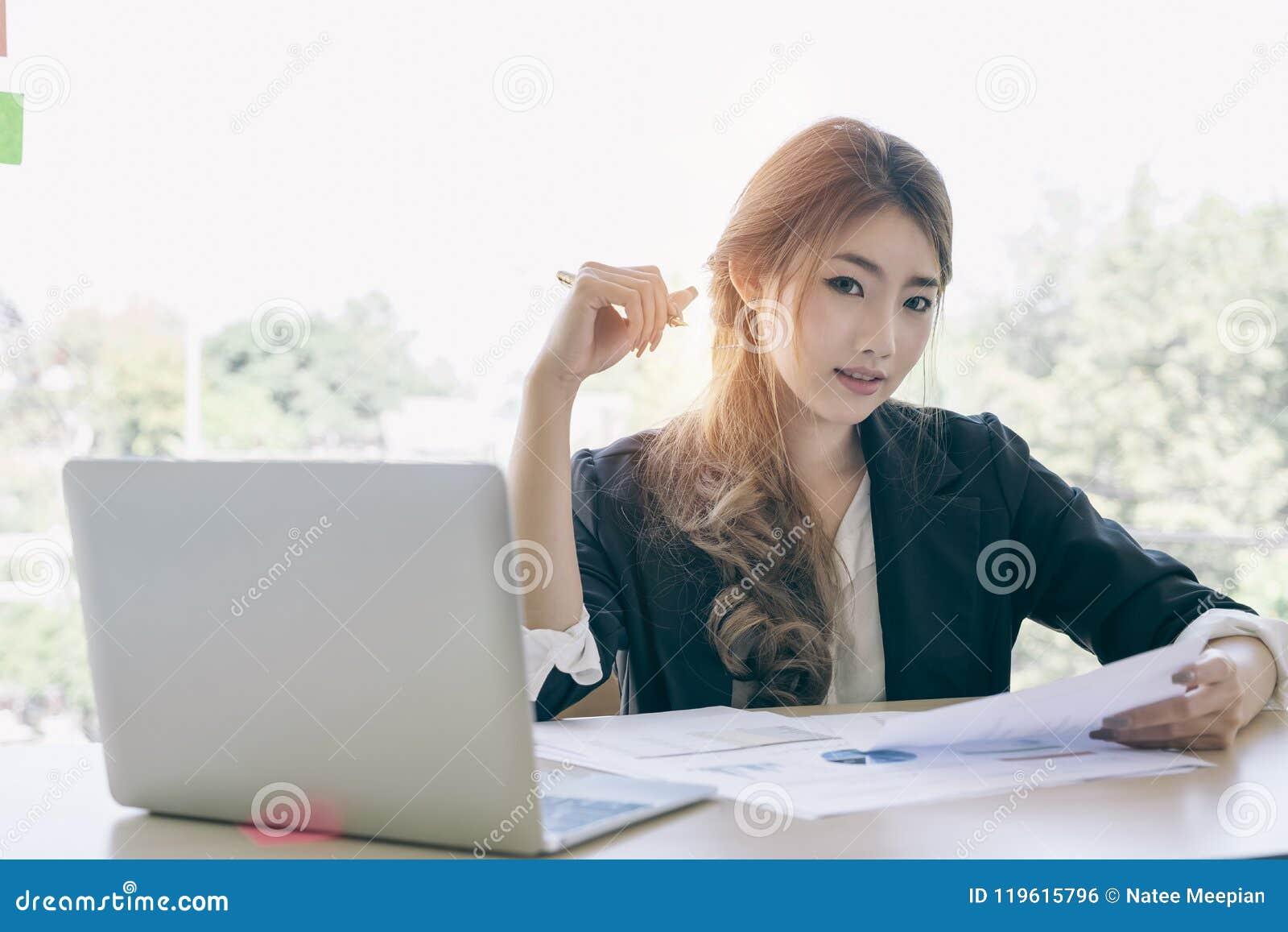 Empresaria joven asiática atractiva que trabaja en el ordenador portátil mientras que sea