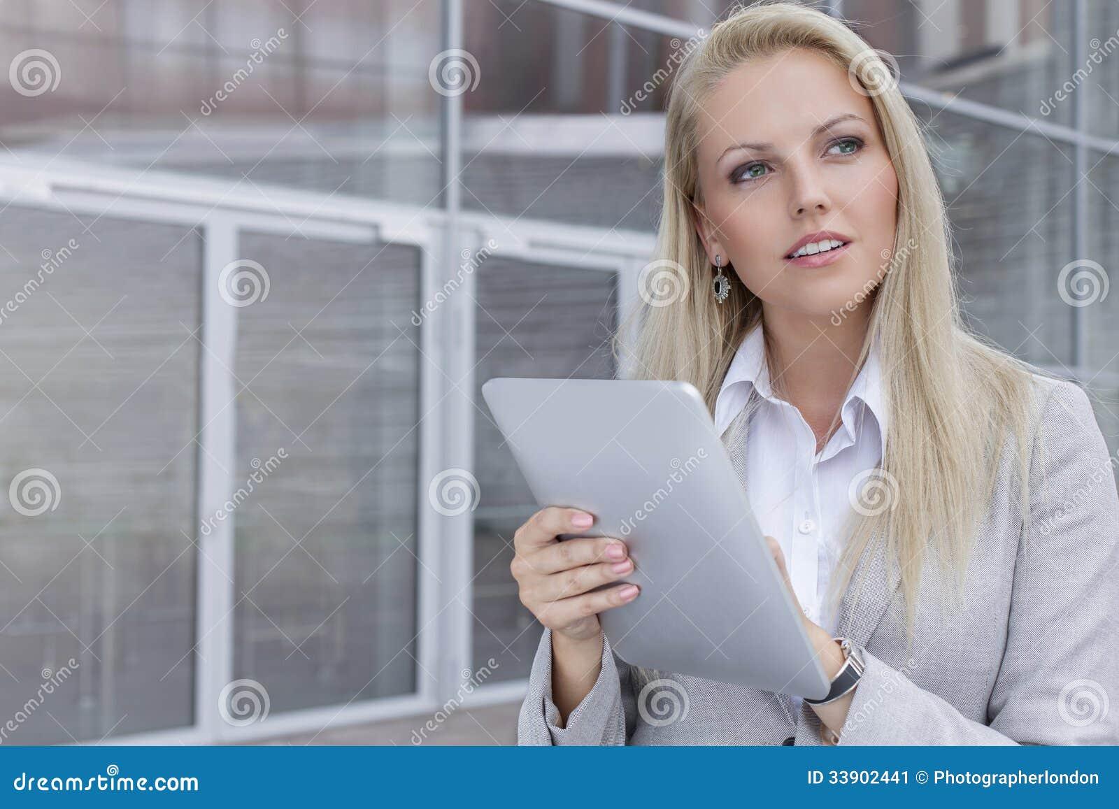 Empresaria joven pensativa que usa la tableta digital mientras que mira lejos contra el edificio de oficinas