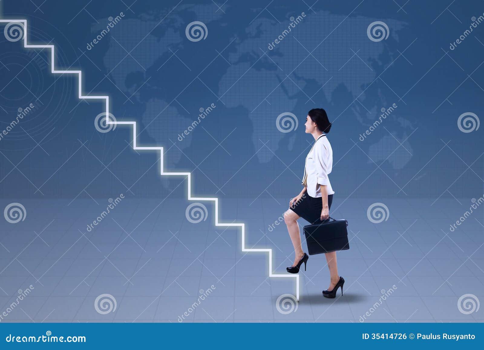 Empresaria joven que camina para arriba en las escaleras