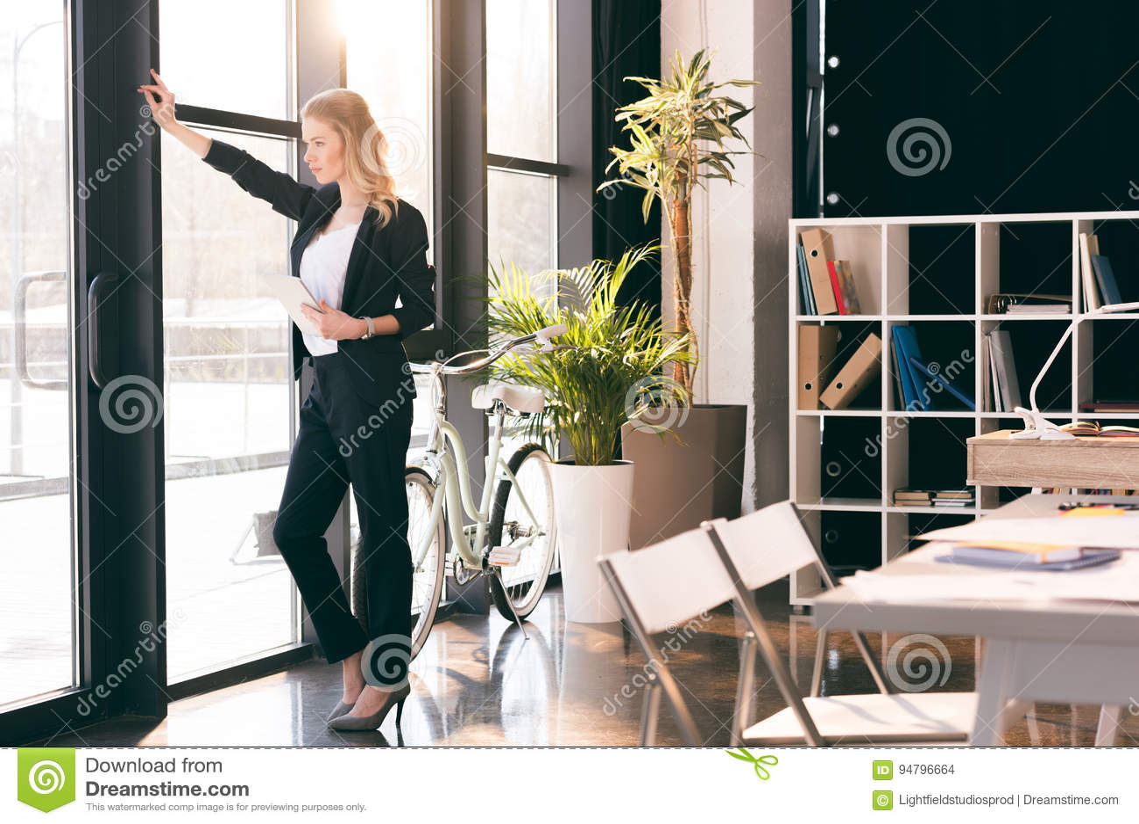 Empresaria joven que sostiene la tableta digital y que mira la ventana en oficina moderna