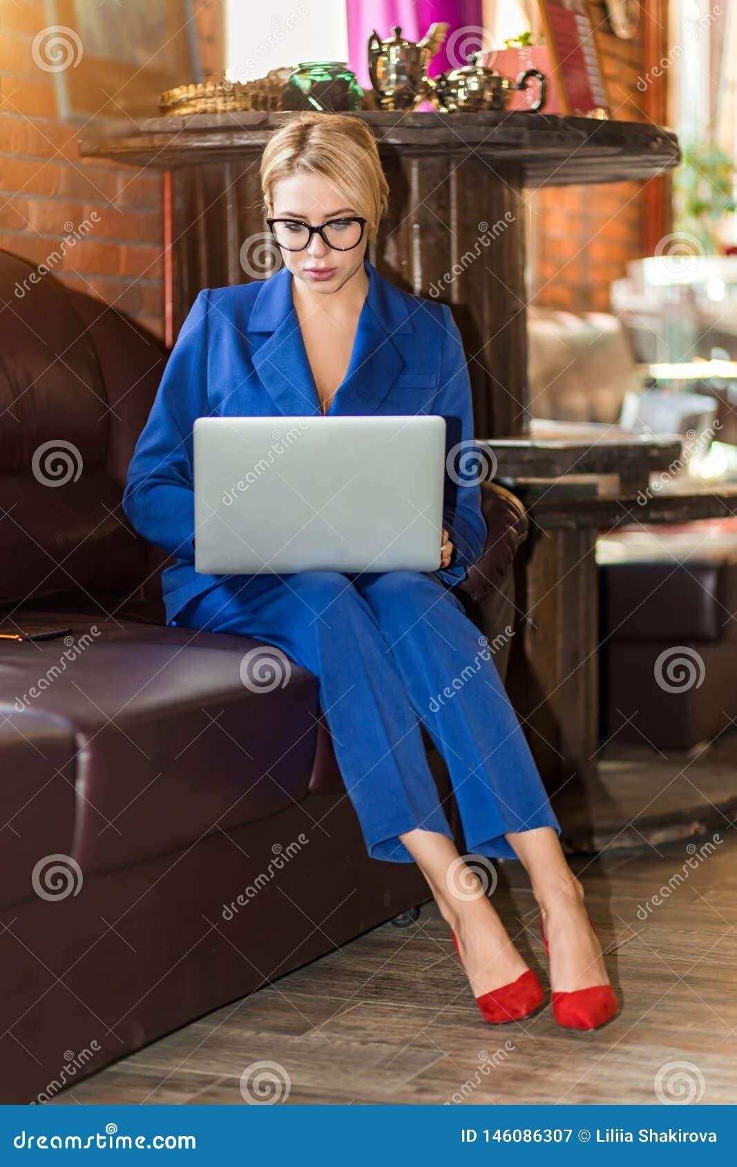 Empresaria joven que trabaja la sentada en l?nea en el sof?