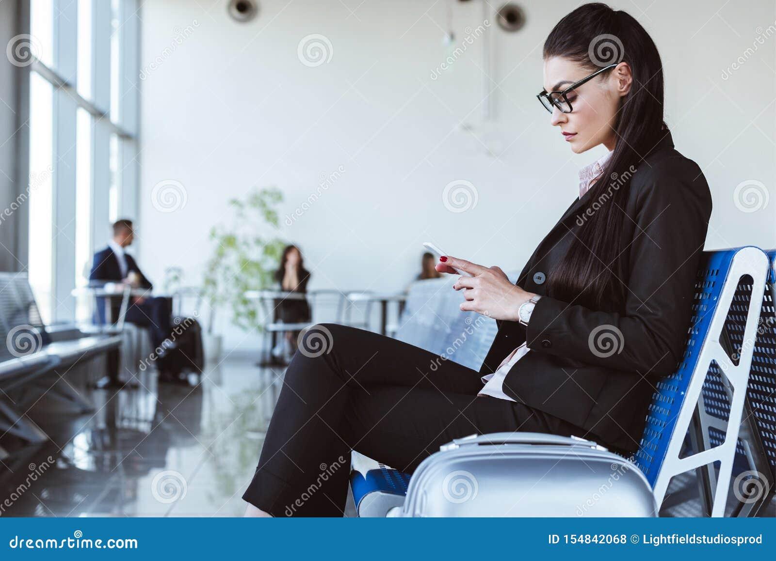 Empresaria joven que usa smartphone en el salón de la salida