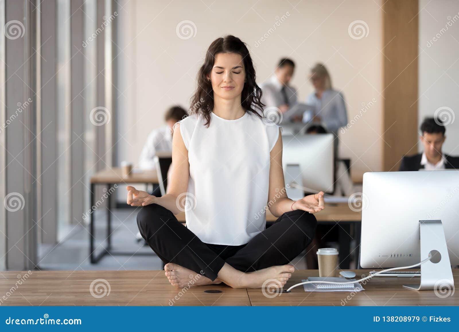 Empresaria joven tranquila que hace ejercicio de la yoga en el escritorio del trabajo