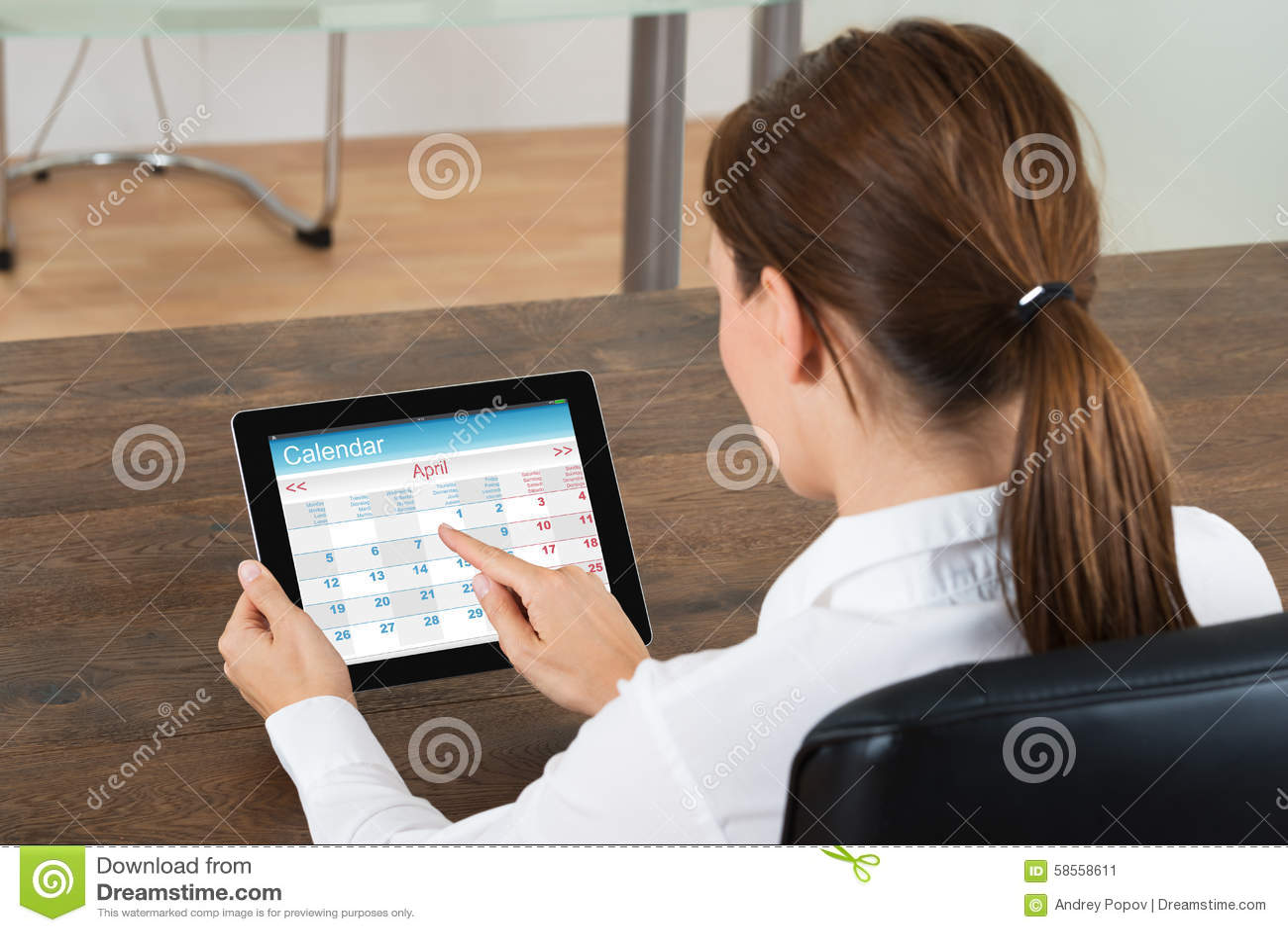 Empresaria Looking At Calendar en la tableta de Digitaces