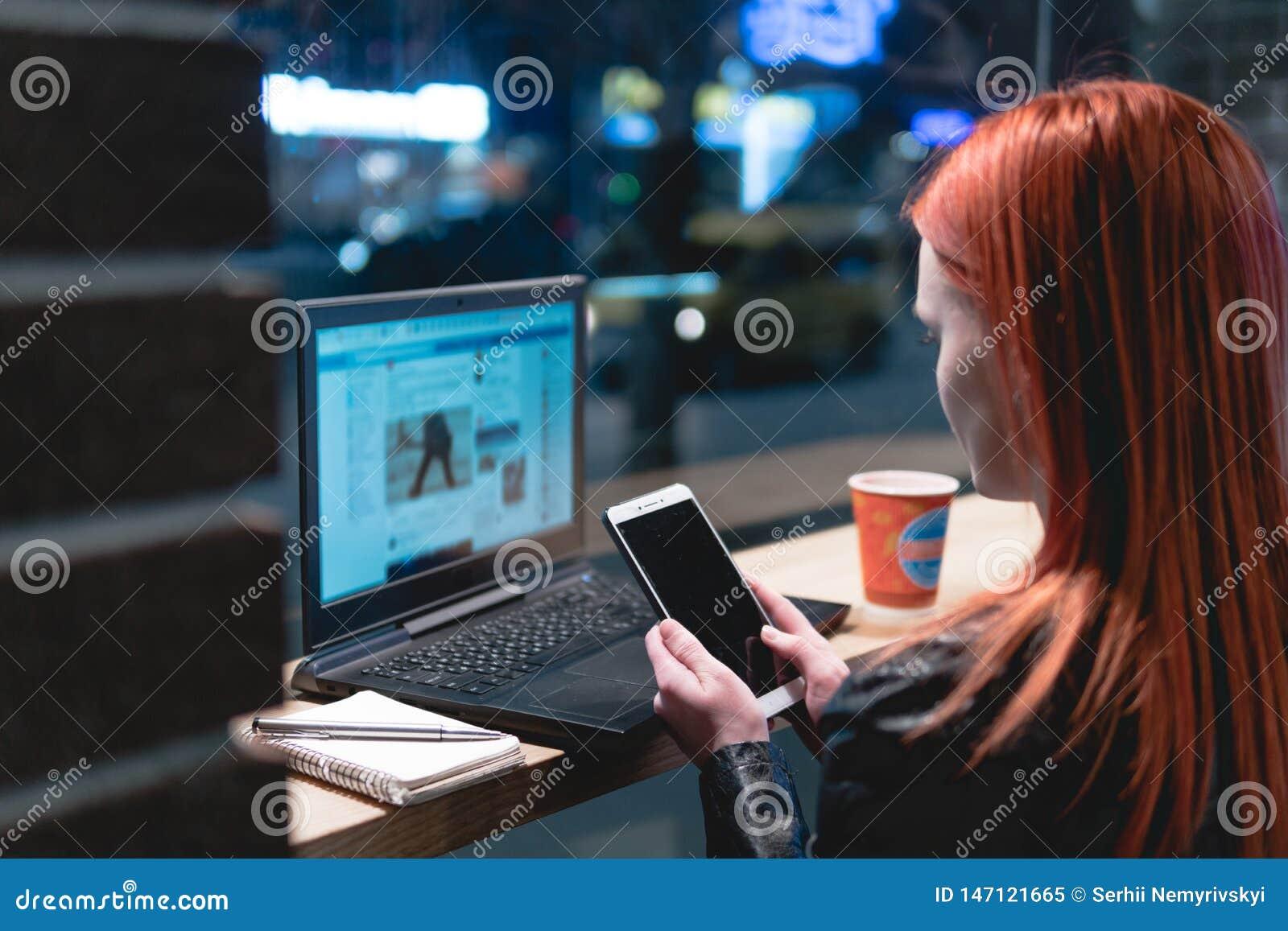 Empresaria, muchacha que trabaja en el ordenador port?til en el caf?, smartphone en manos, pluma, tel?fono del control del uso El