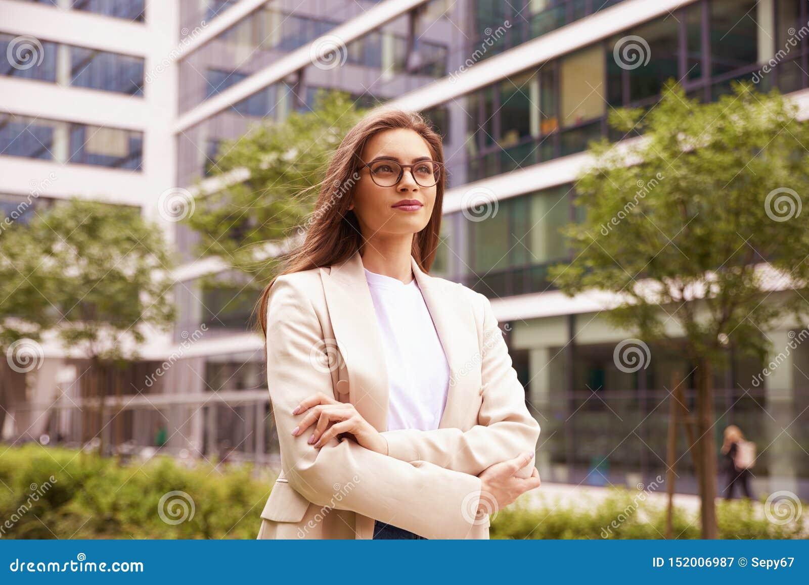 Empresaria que camina en la calle entre los edificios de oficinas
