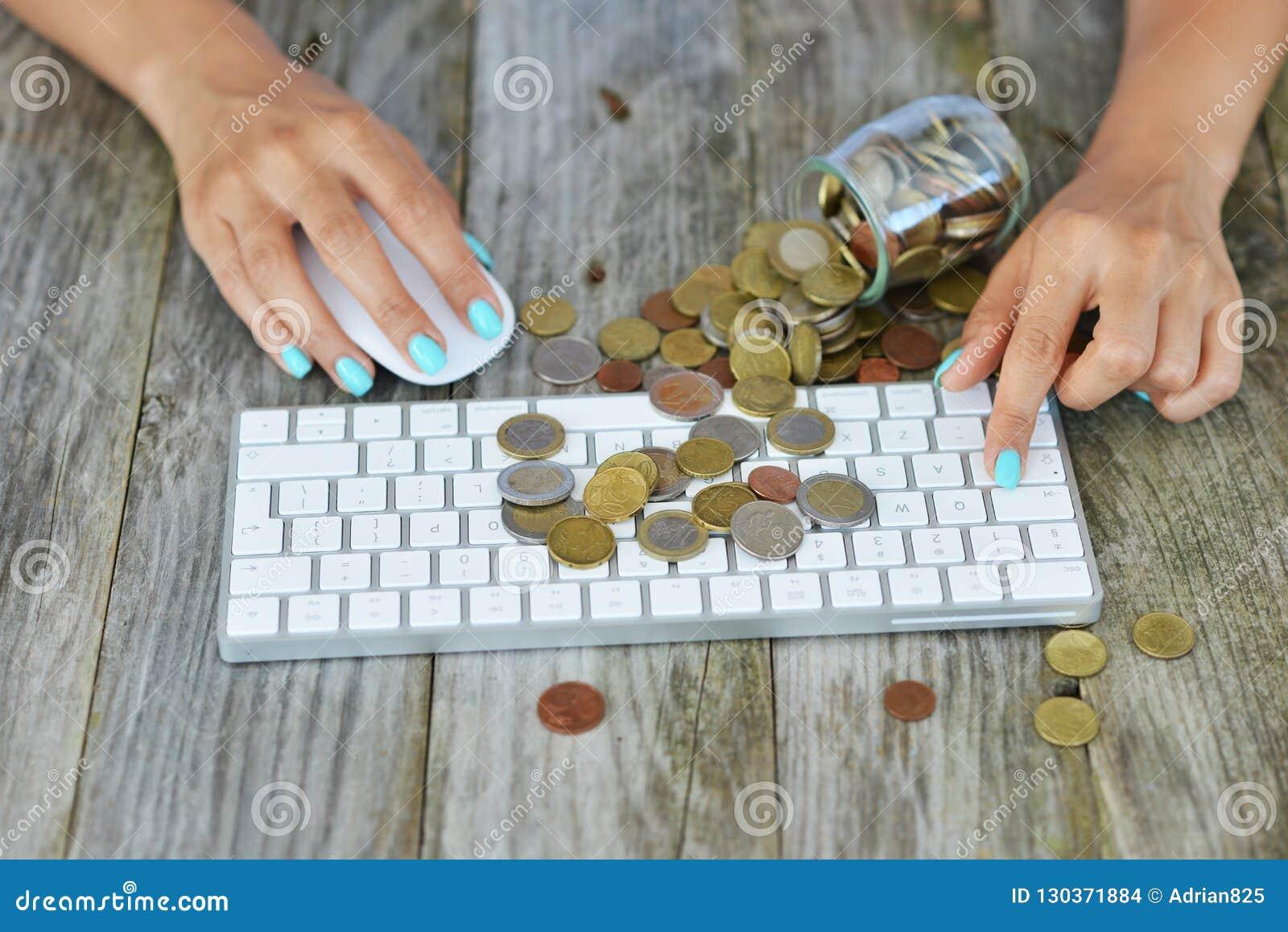Empresaria que hace el dinero en línea, con las monedas del efectivo en el teclado de ordenador, concepto en línea de la transacc
