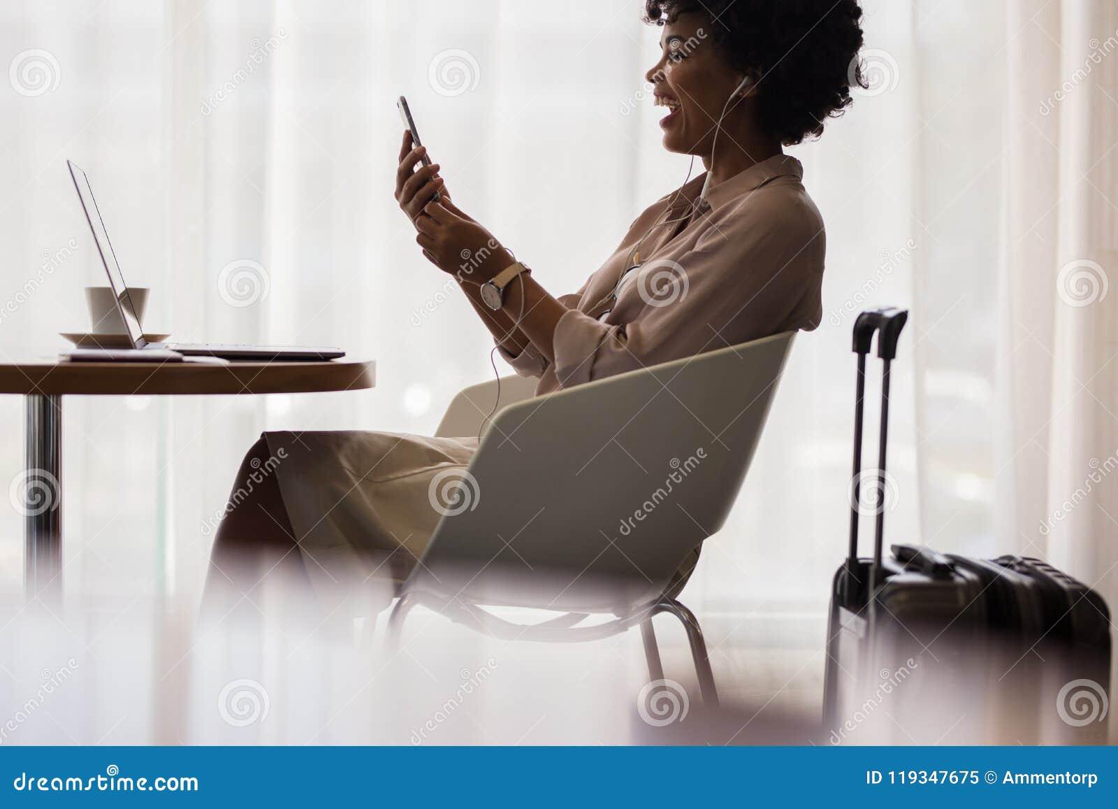 Empresaria que hace la llamada video en el salón del aeropuerto