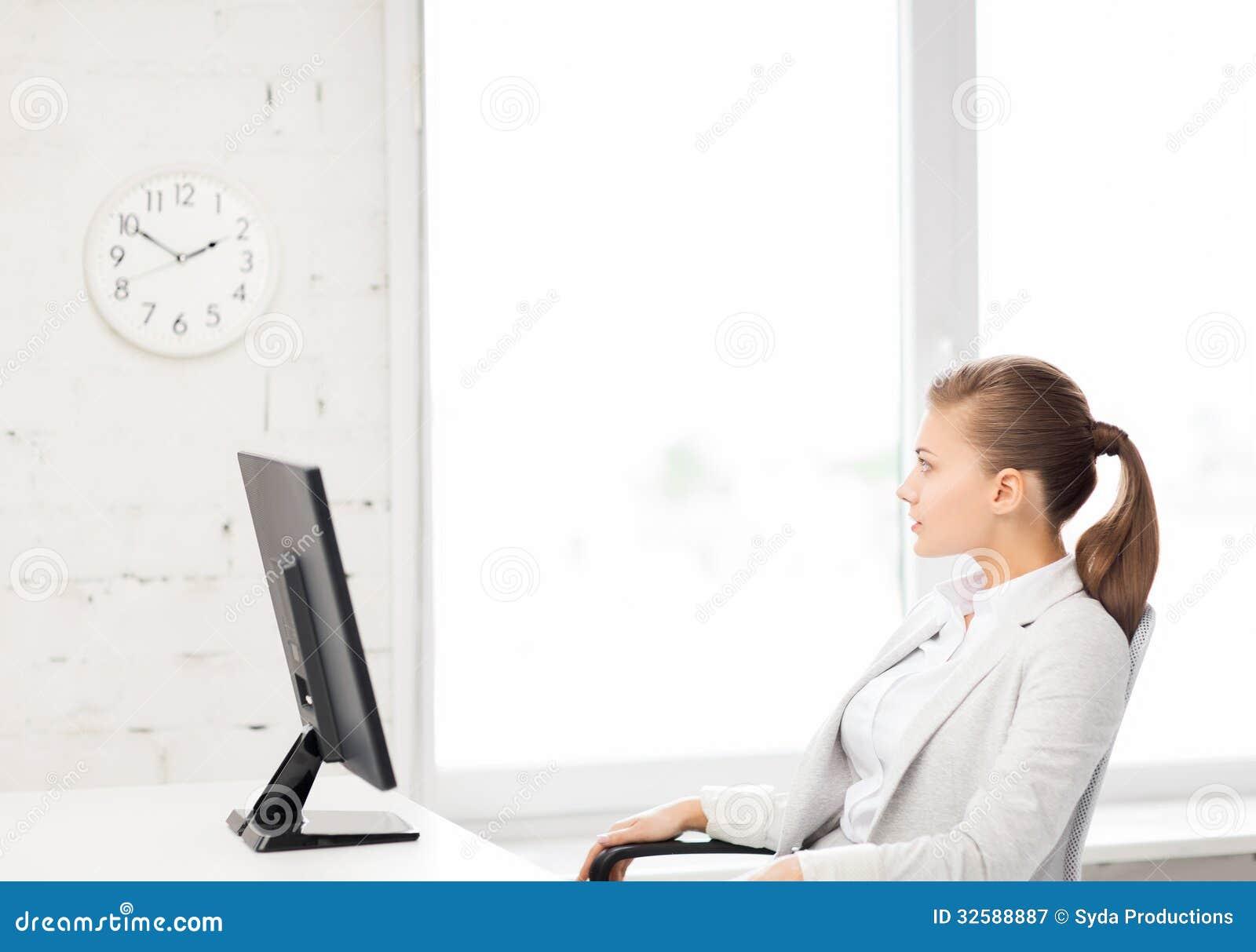 Empresaria que mira el reloj de pared en oficina