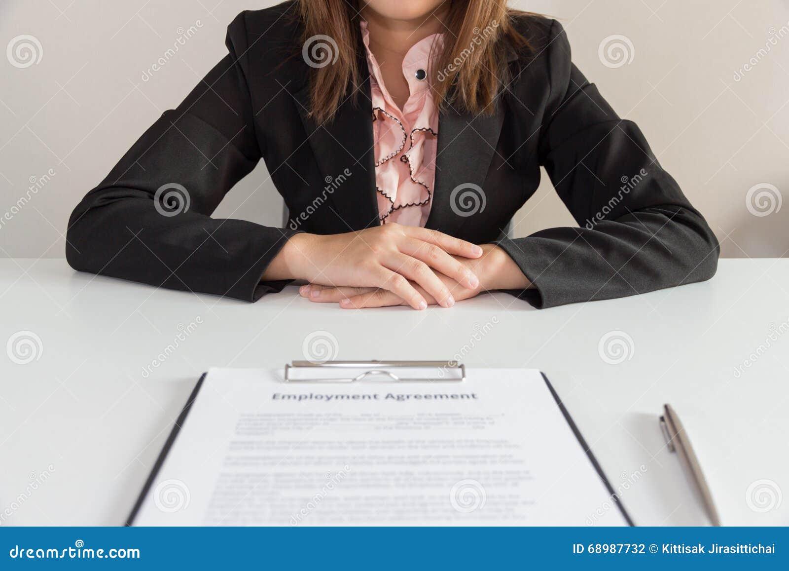 Empresaria que se sienta con el acuerdo de empleo delante de ella