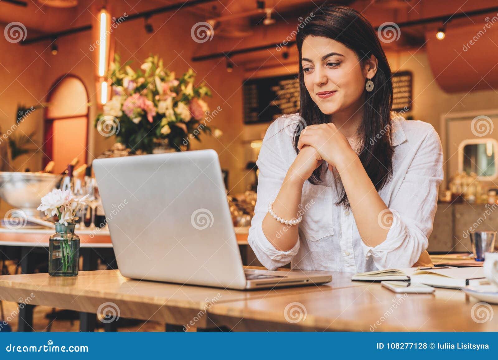 Empresaria que se sienta en café en la tabla, mirando en la pantalla del ordenador, sonriendo Trabajo de la distancia Márketing e