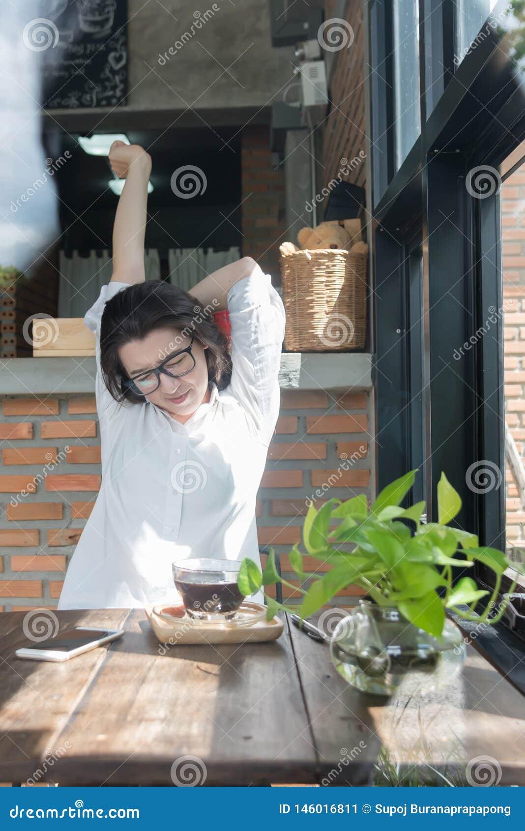 Empresaria que se sienta en su lugar de trabajo y que estira sus manos sobre su cabeza Empleado de sexo femenino cansado en el lu
