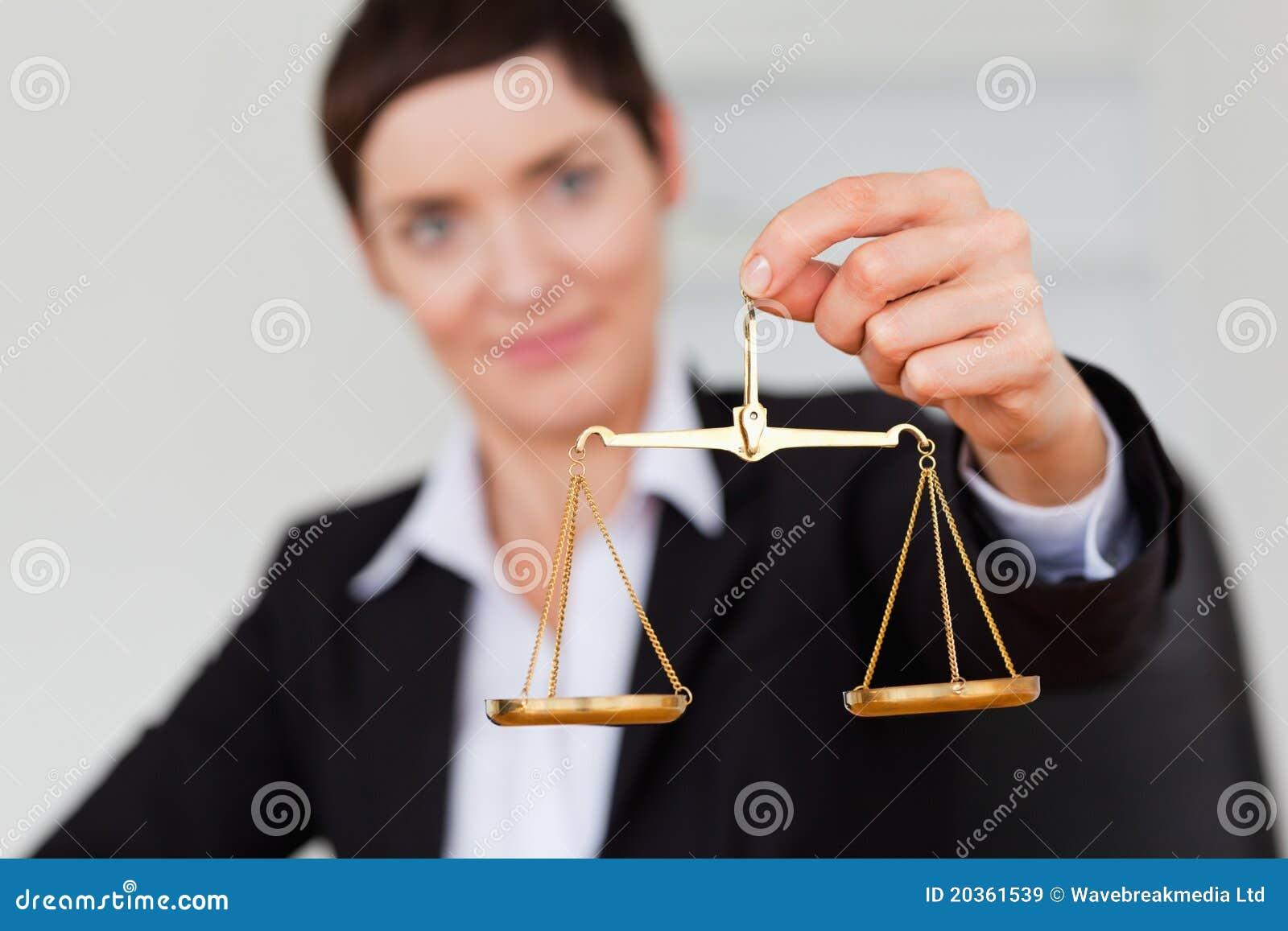 Empresaria seria que sostiene la escala de la justicia