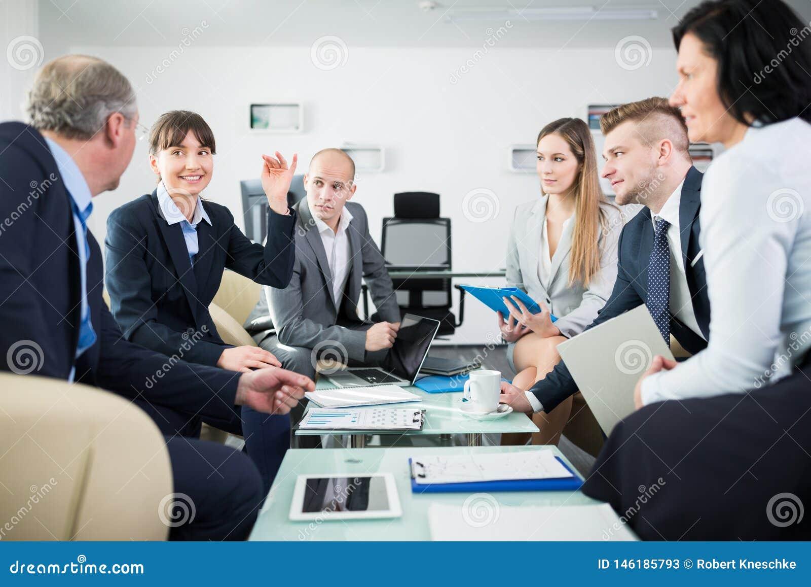 Empresaria sonriente Discussing With Colleagues en oficina