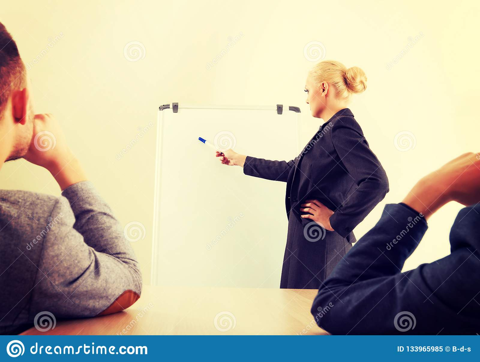 Empresaria sonriente que dibuja un gráfico para sus colegas en el whiteboard
