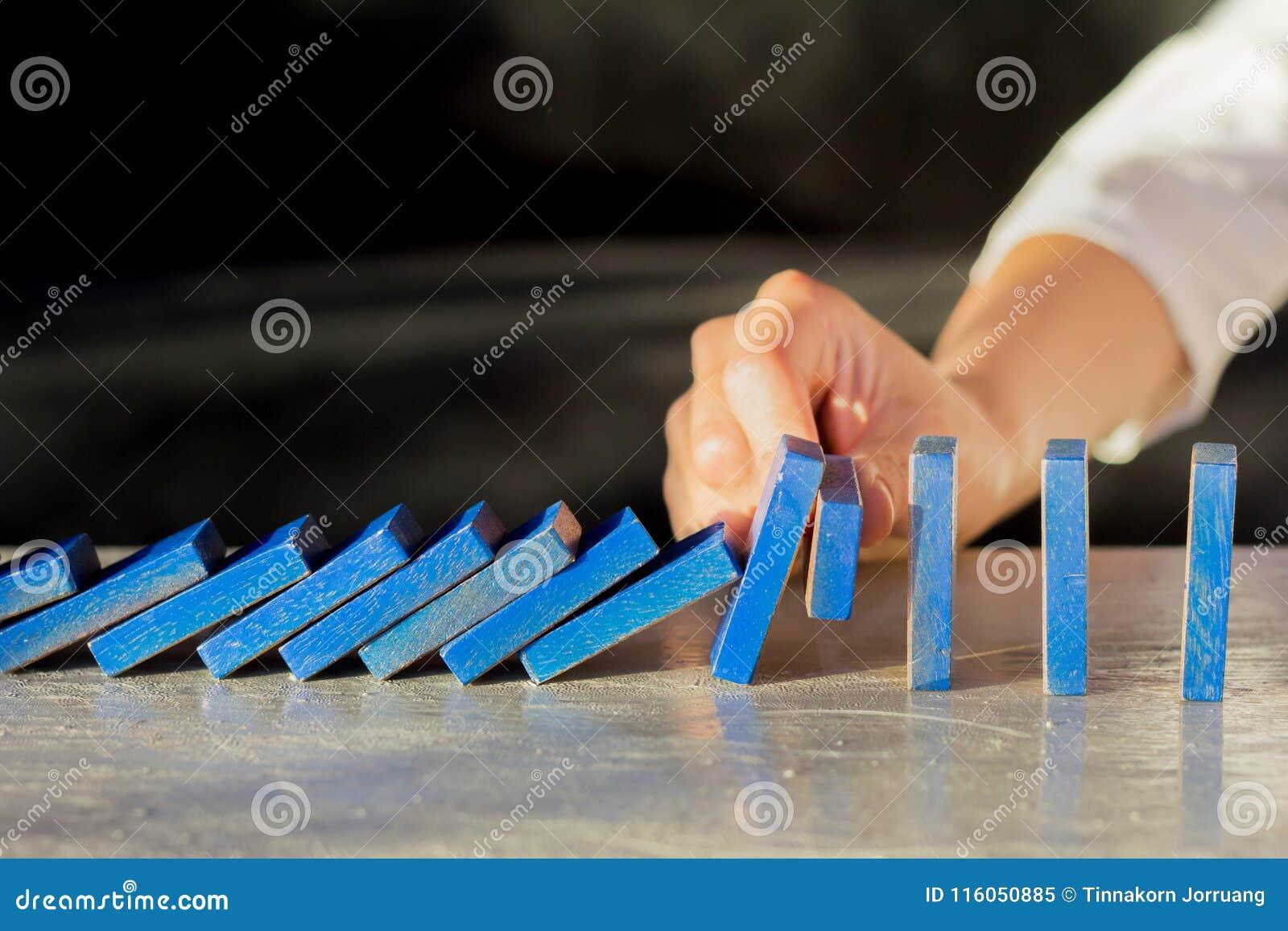 Empresaria Stopping The Effect del dominó con la mano en el escritorio