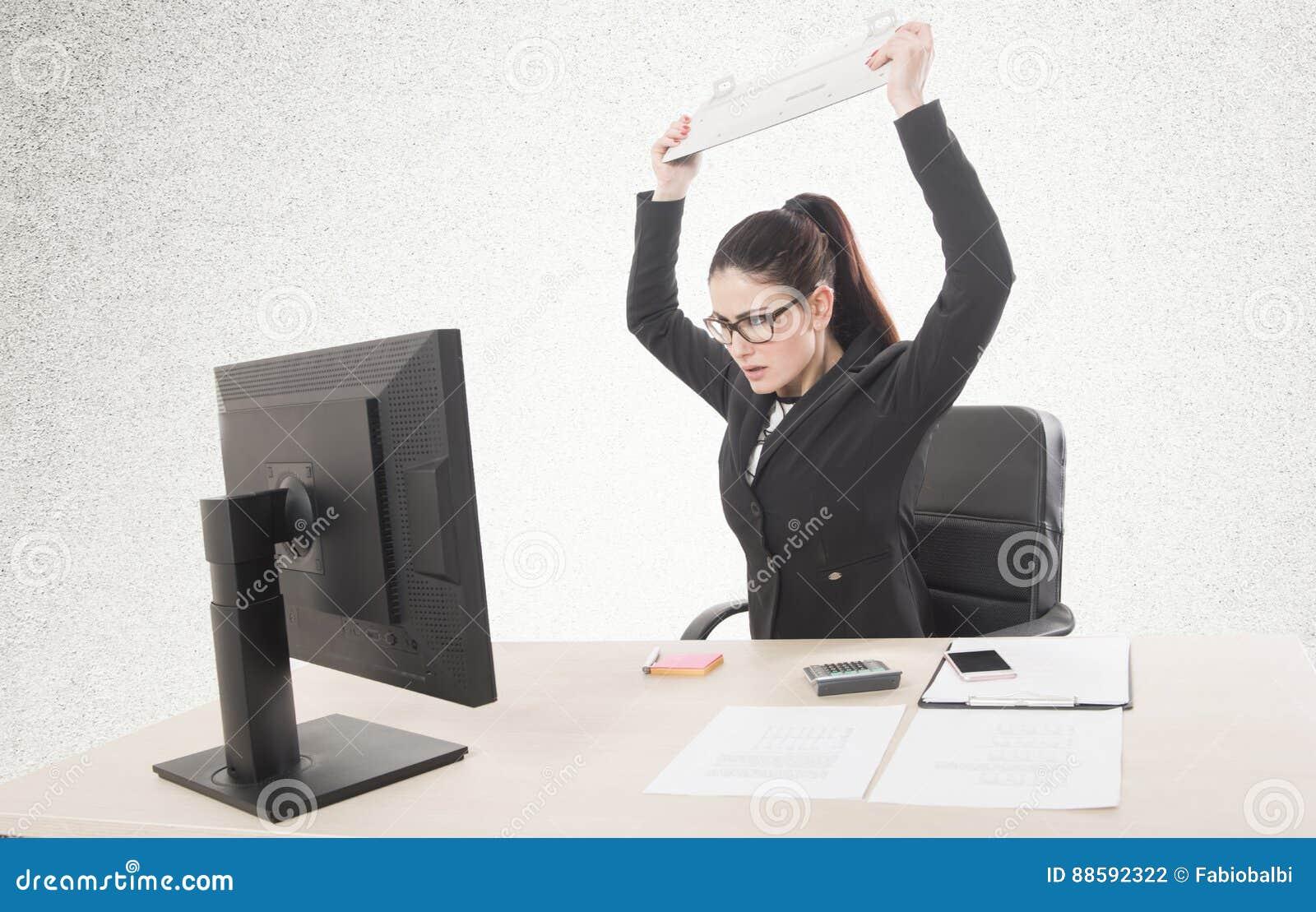 Empresaria subrayada que se sienta en la tabla delante de los ordenadores