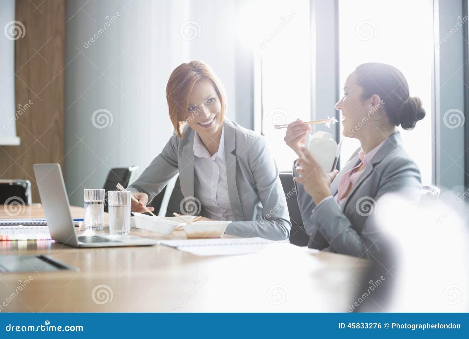 Empresarias jovenes sonrientes que almuerzan en la tabla en oficina
