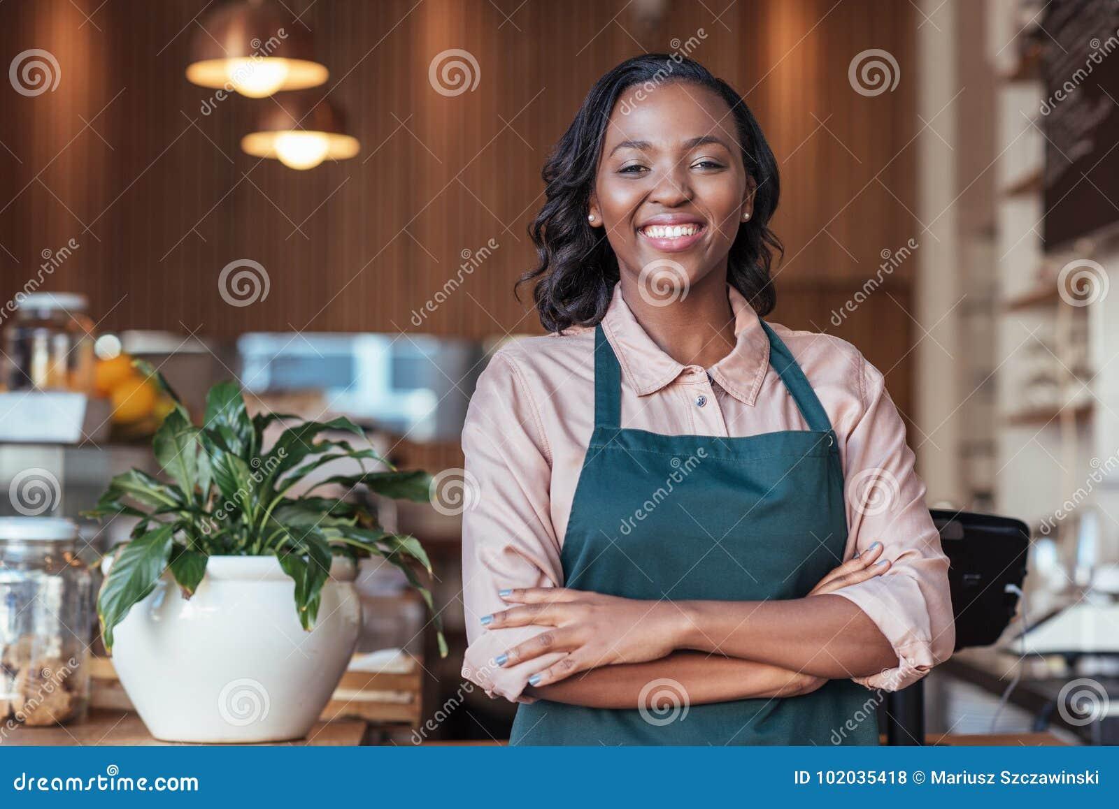Empresario africano sonriente que se coloca en el contador de su café