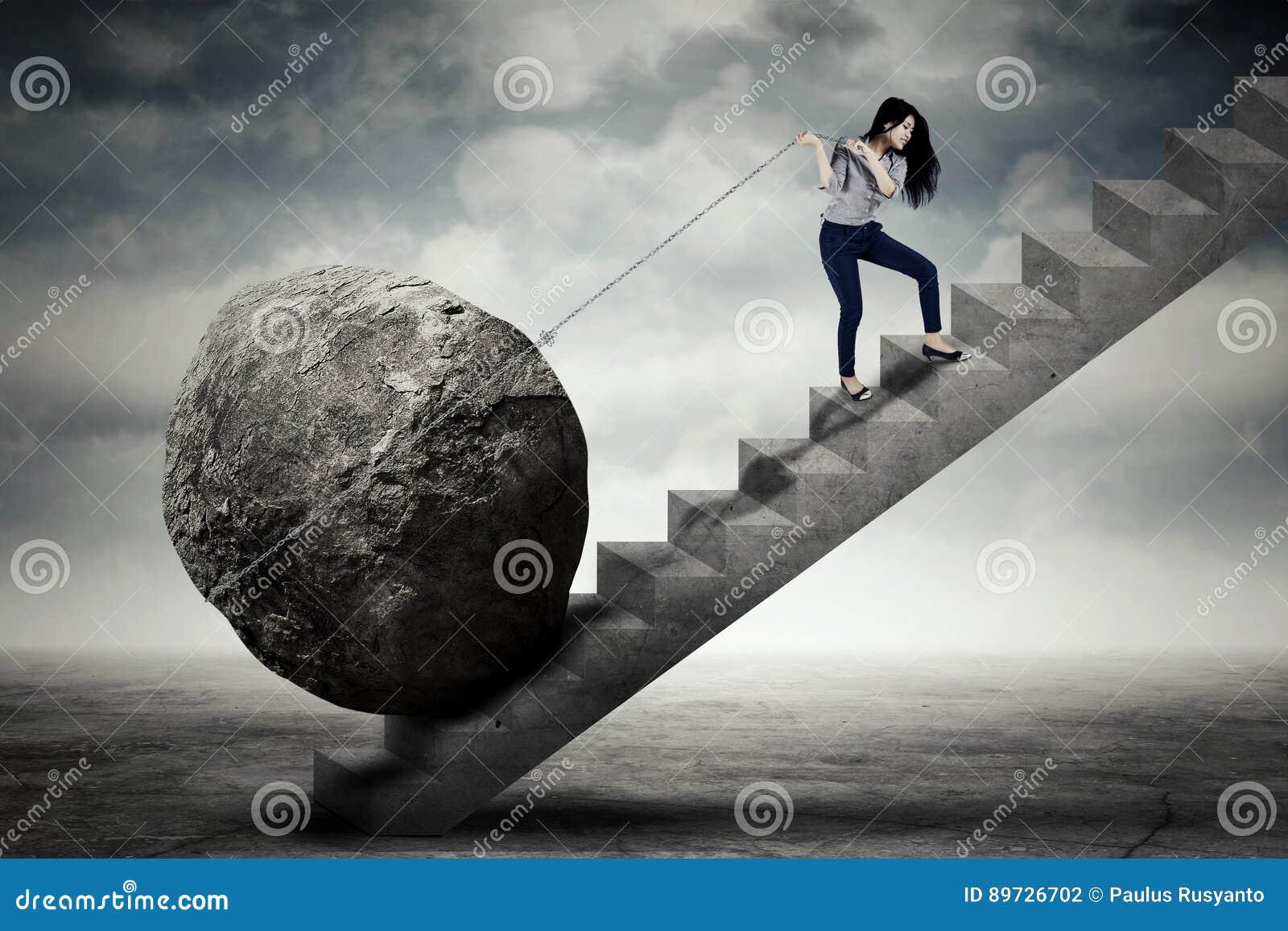 Empresario de sexo femenino que lleva la piedra grande en la escalera