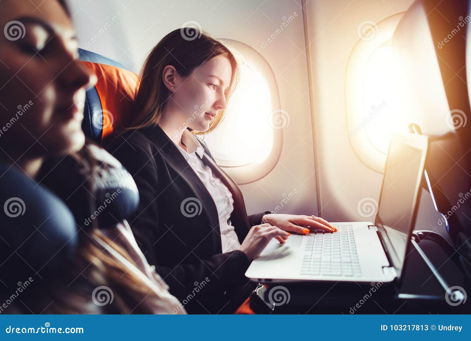 Empresario de sexo femenino que trabaja en el ordenador portátil que se sienta cerca de ventana en un aeroplano