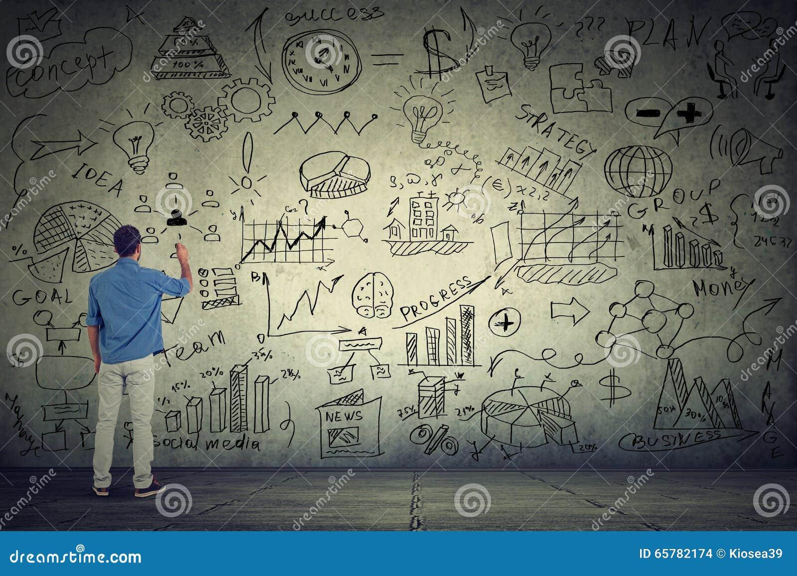 Empresario del hombre de negocios que escribe algunos nuevos cálculos del proyecto en la pared gris