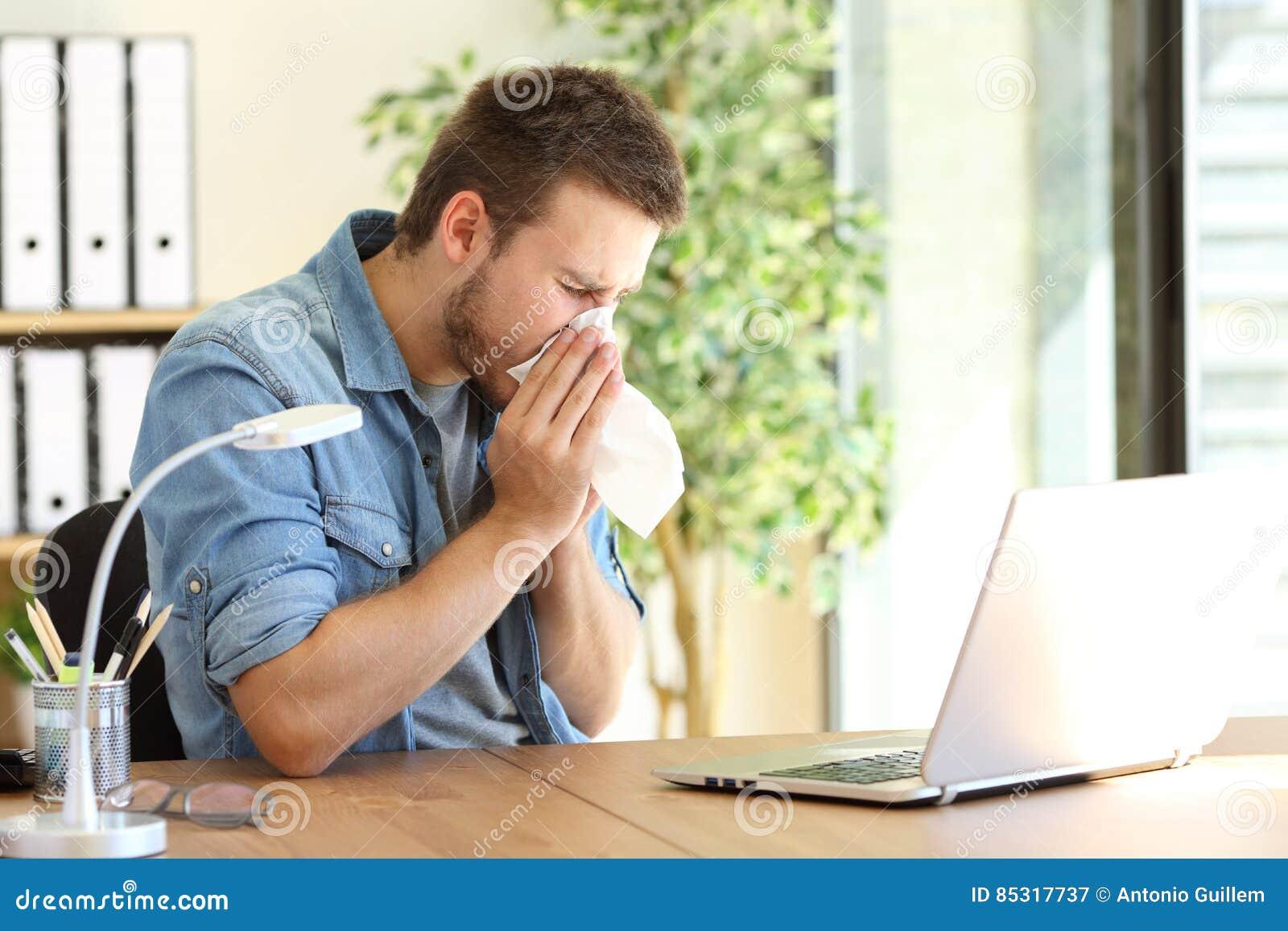 Empresario enfermo que estornuda en la oficina