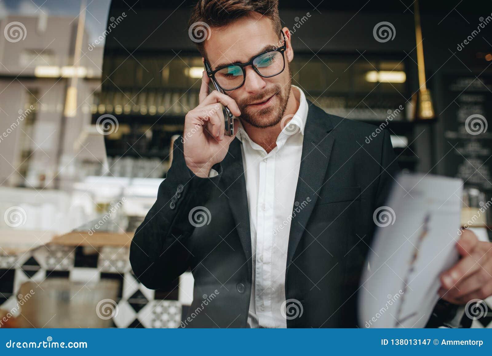Empresario que habla en el teléfono celular que mira los papeles de la oficina en a