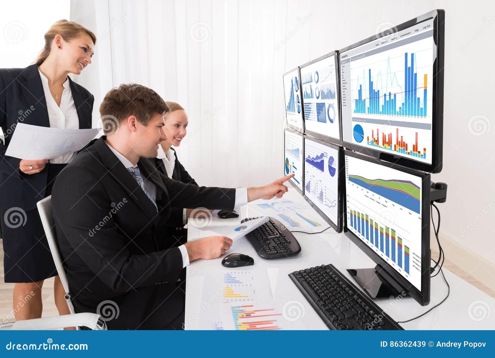 Empresarios que analizan gráficos en los ordenadores múltiples
