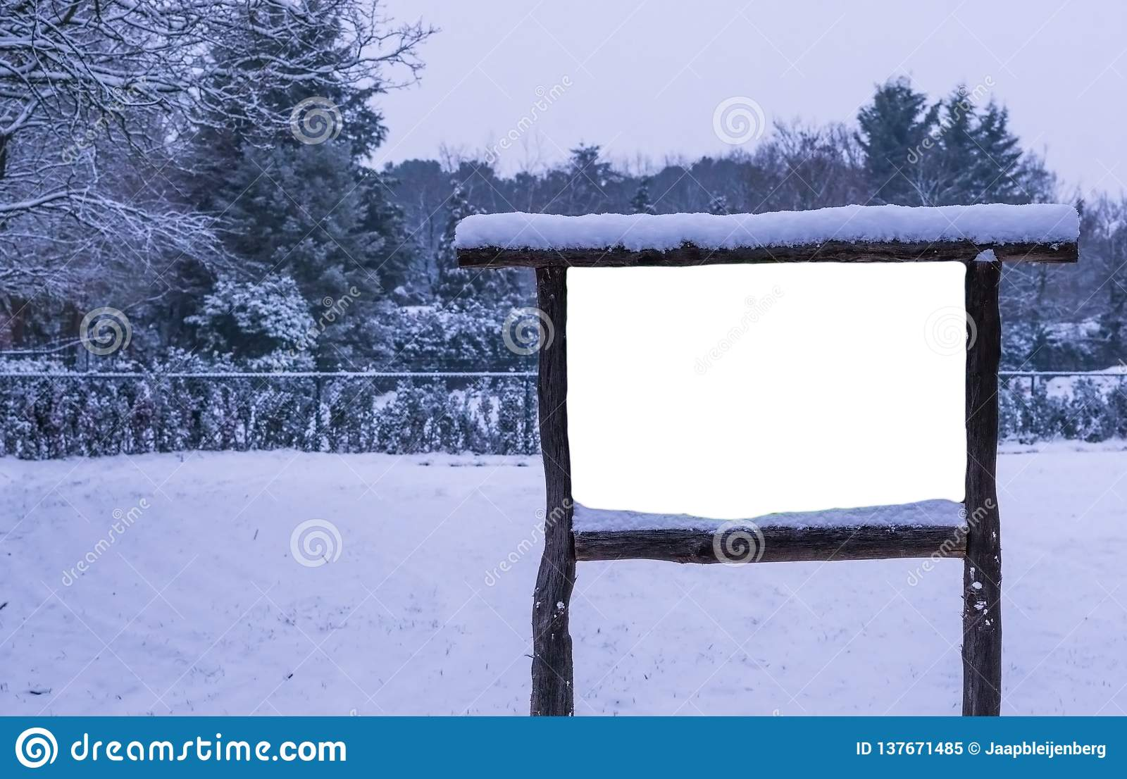Empty and blank wooden advertisement board covered in snow, winter season in the forest, publicity billboard