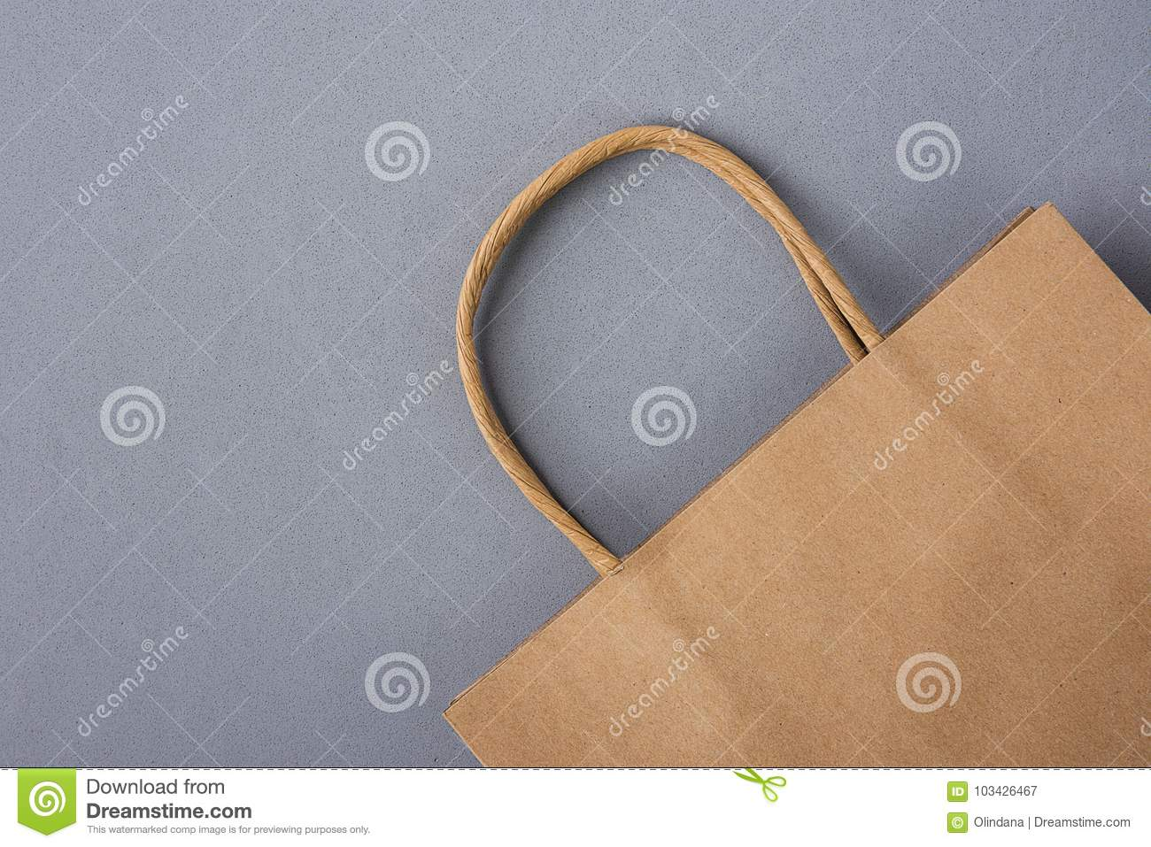 Empty Brown Craft Paper Bag on Gray Background. Sales Discount Shopping. Black Friday Cyber Monday. Christmas Gifts. Copy Space